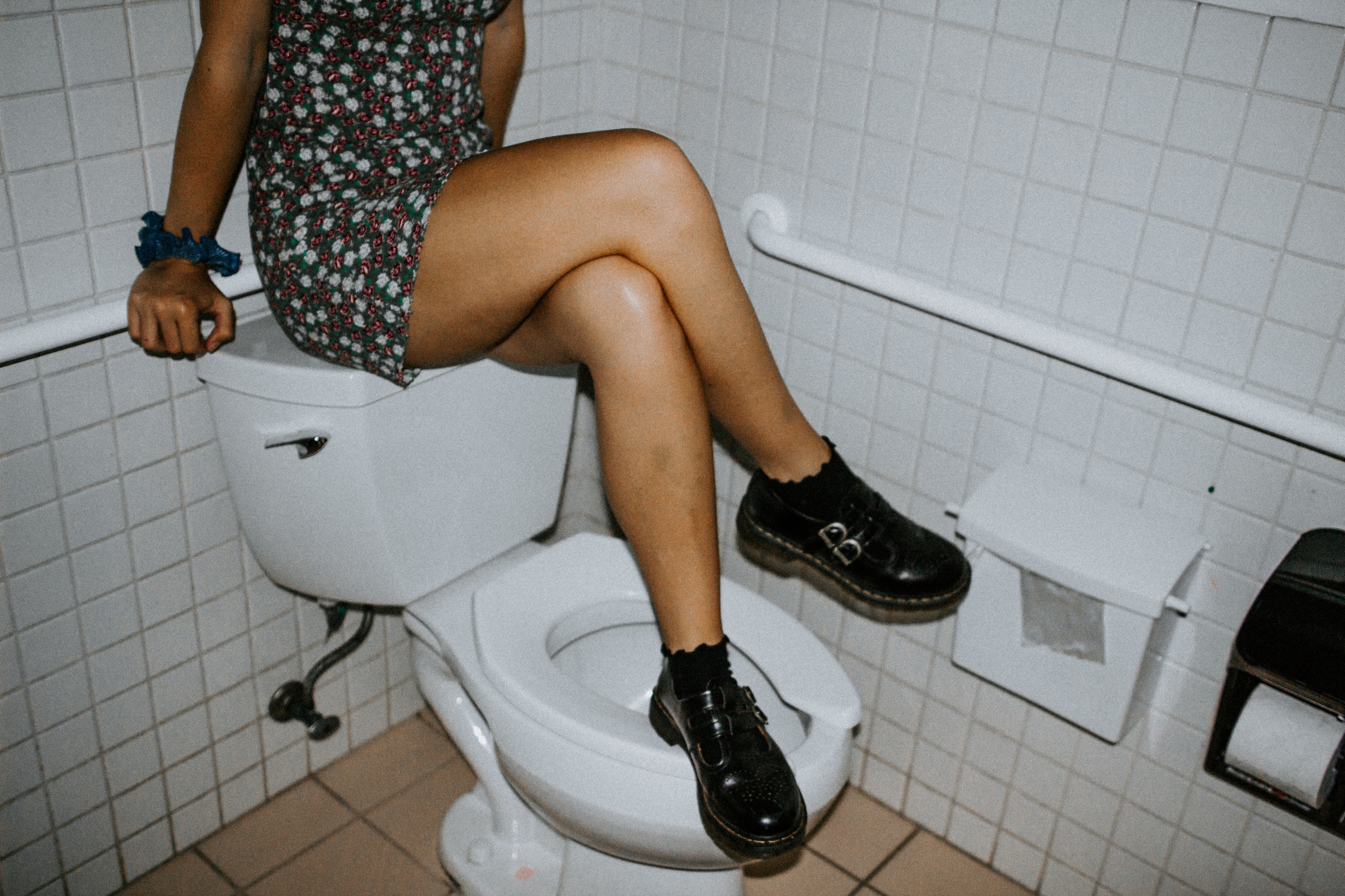 A girl in a mini-dress sits on top of the toilet tank in a public restroom with legs crossed and one of her feet on the seat.