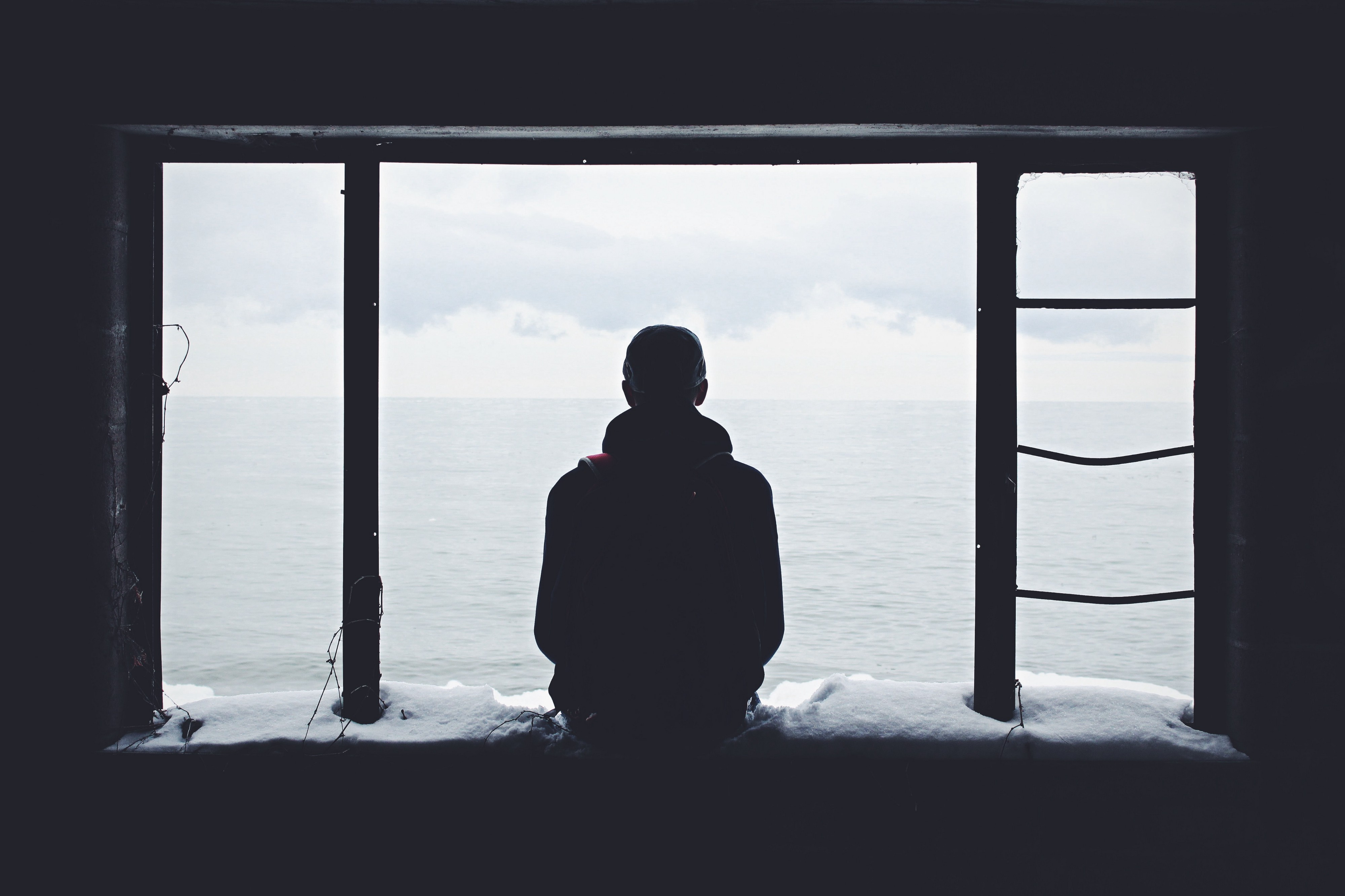 man sitting along looking out window