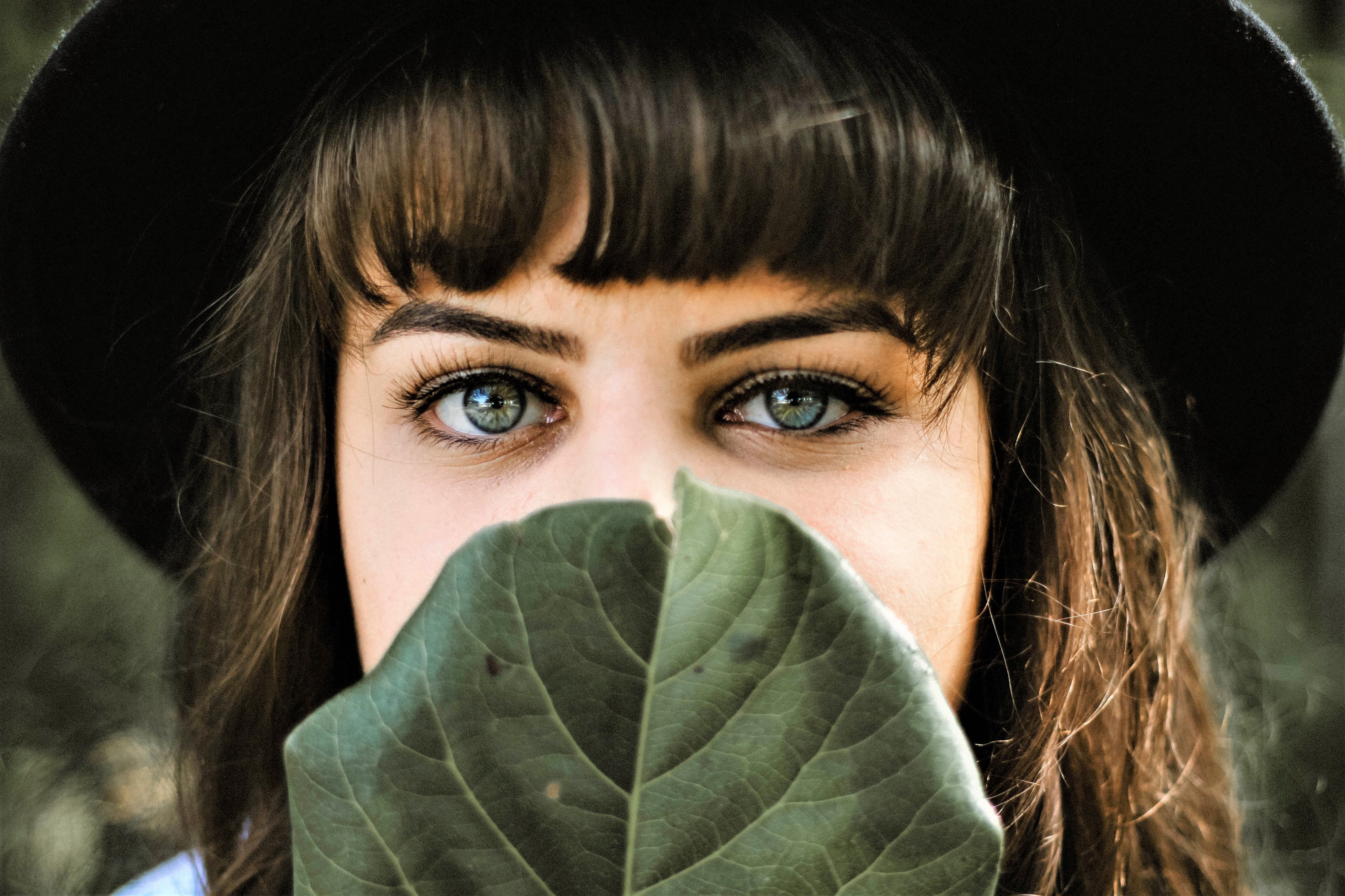 girl with brown hair and green eyes wearing dark hat holding leaf in front of her face