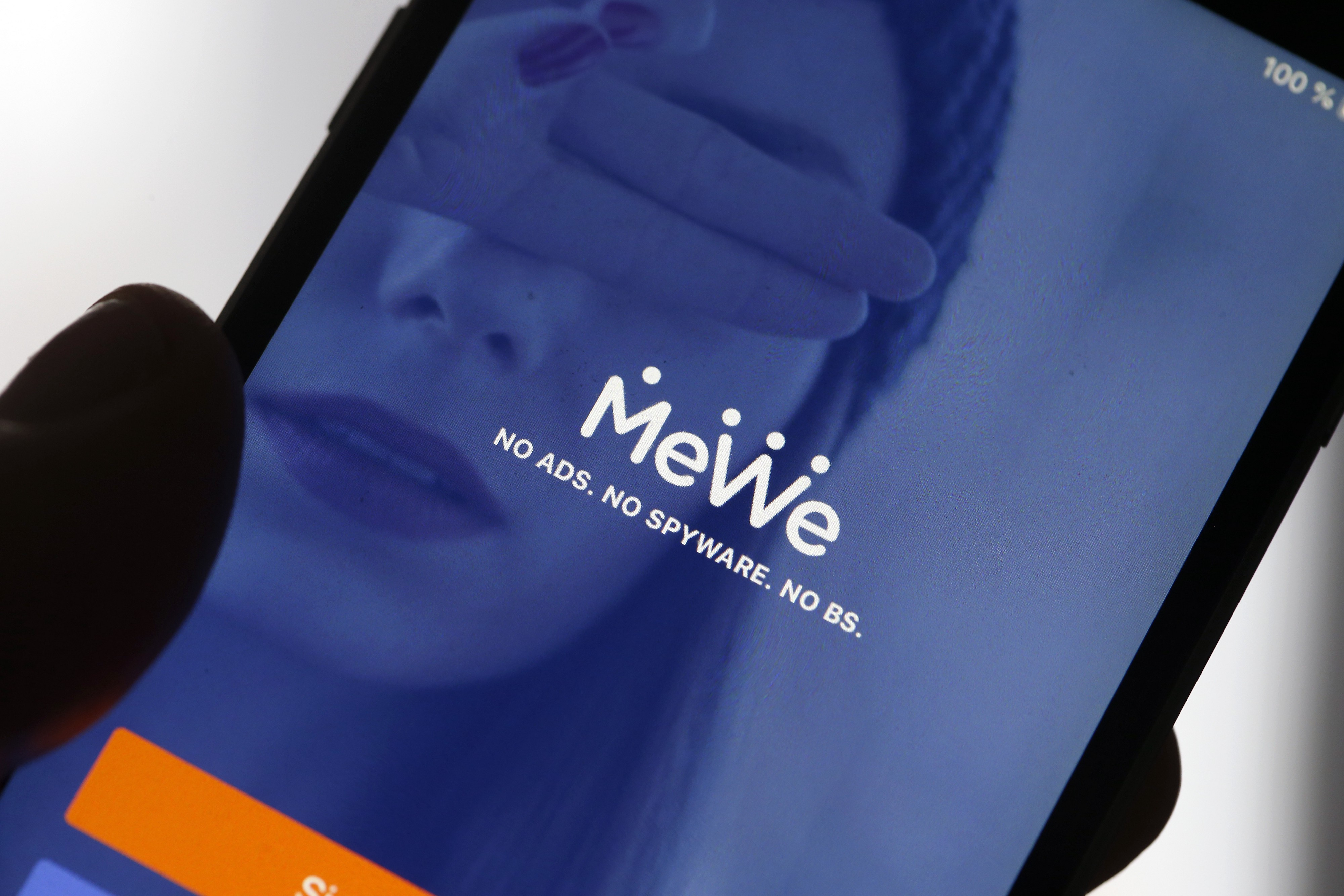 A photo illustration of the home page of the social media application MeWe displayed on the screen of an iPhone.