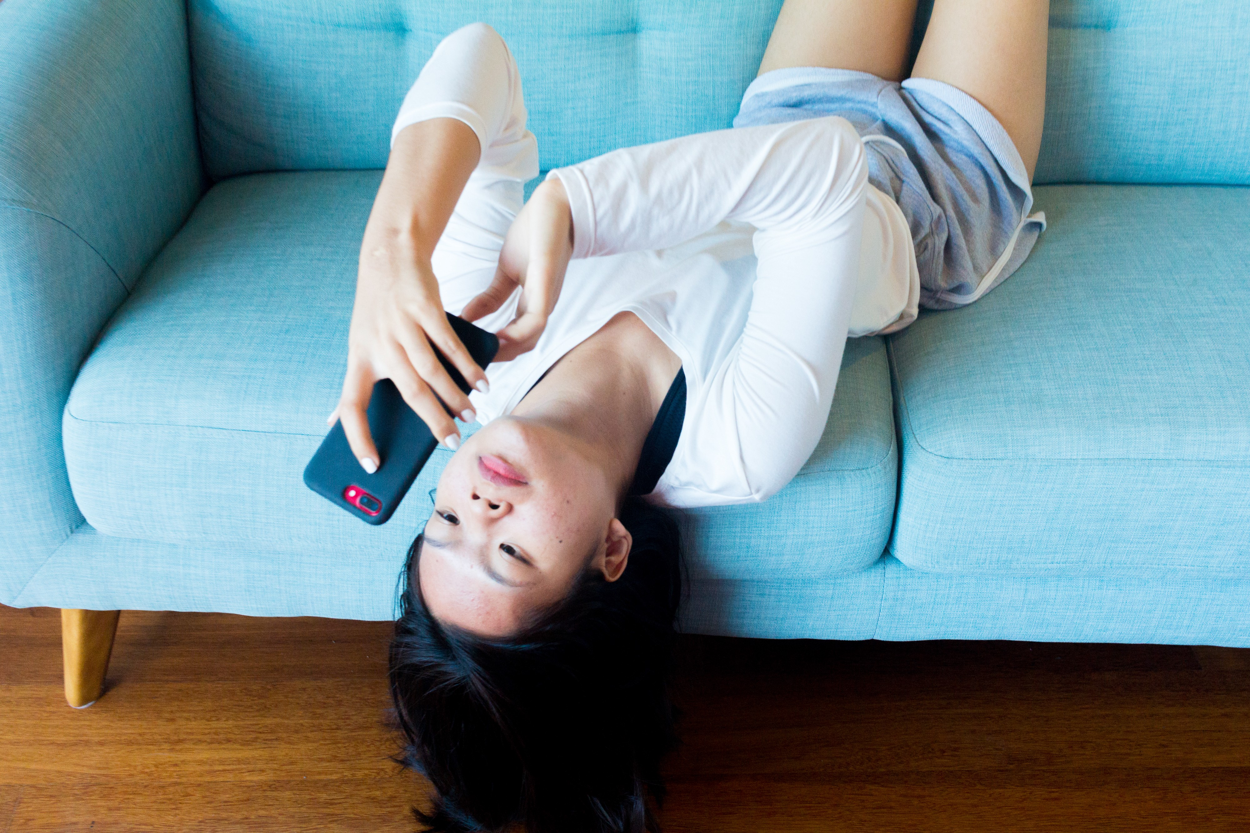 Teenage girl laying down upside down on a couch using her smartphone