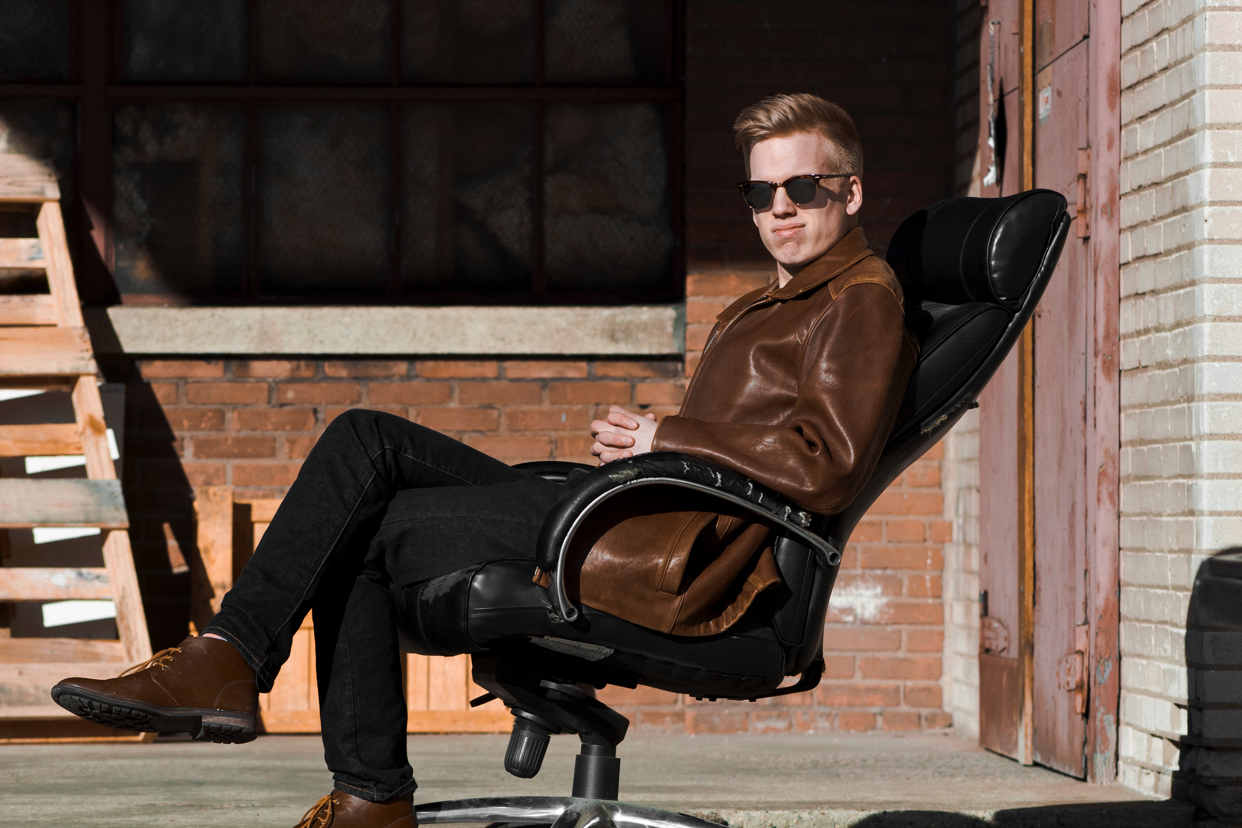 Person wearing brown leather jacket and sunglasses, sitting on black office chair outside