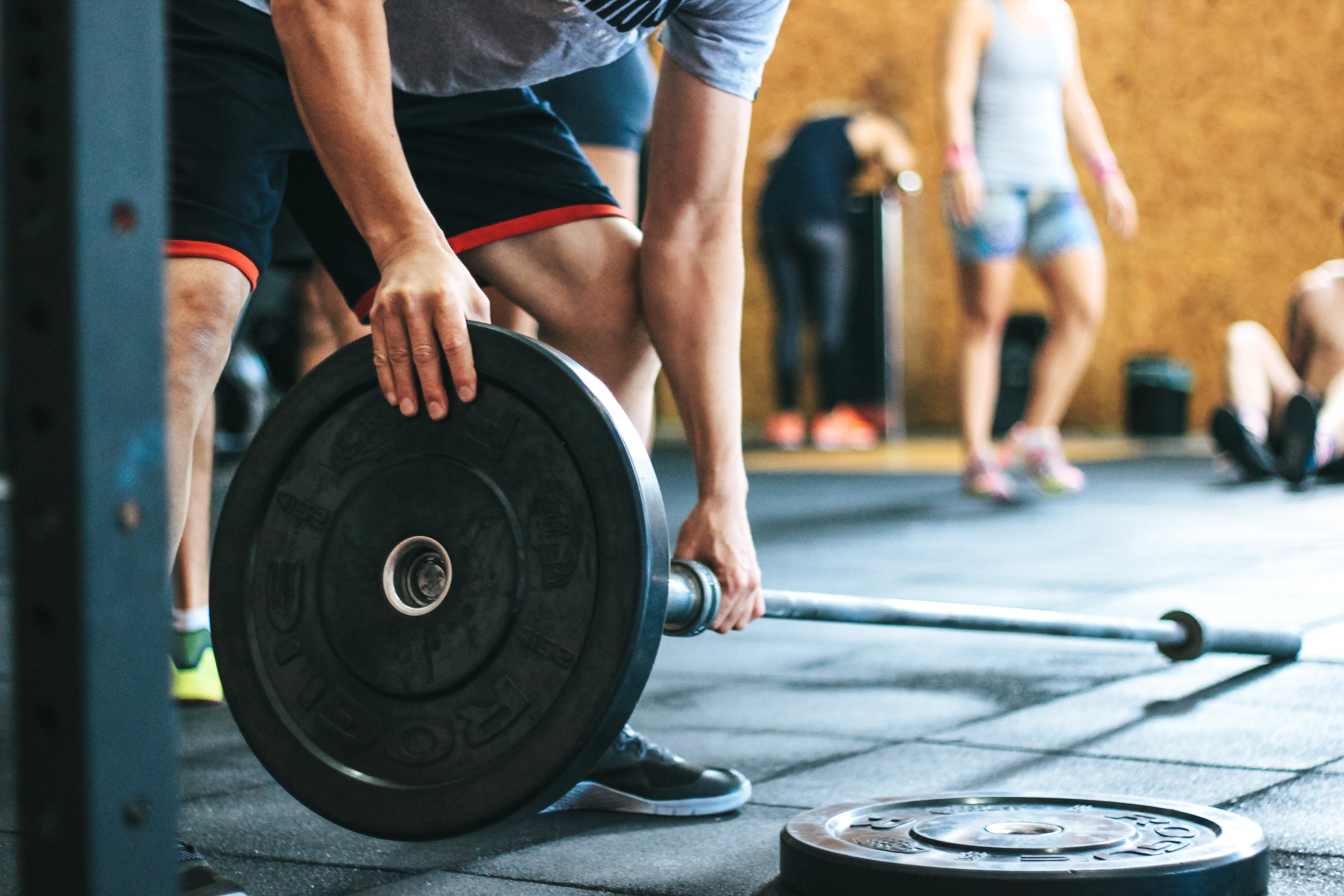 Feature image of article. Someone putting weights on to a barbell.