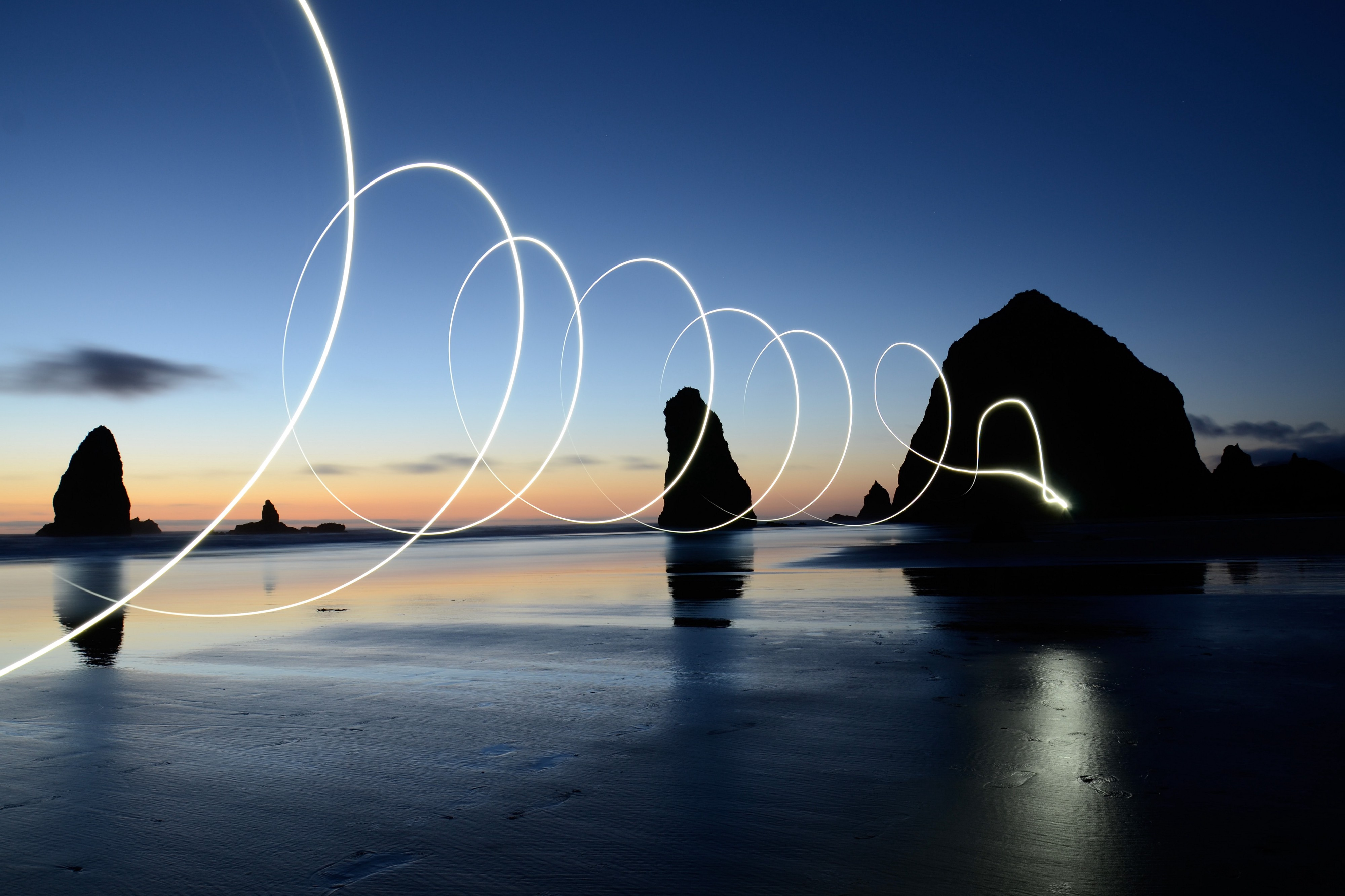 Dusk on a beach with rock formations in the background and a spiraling light going across it all