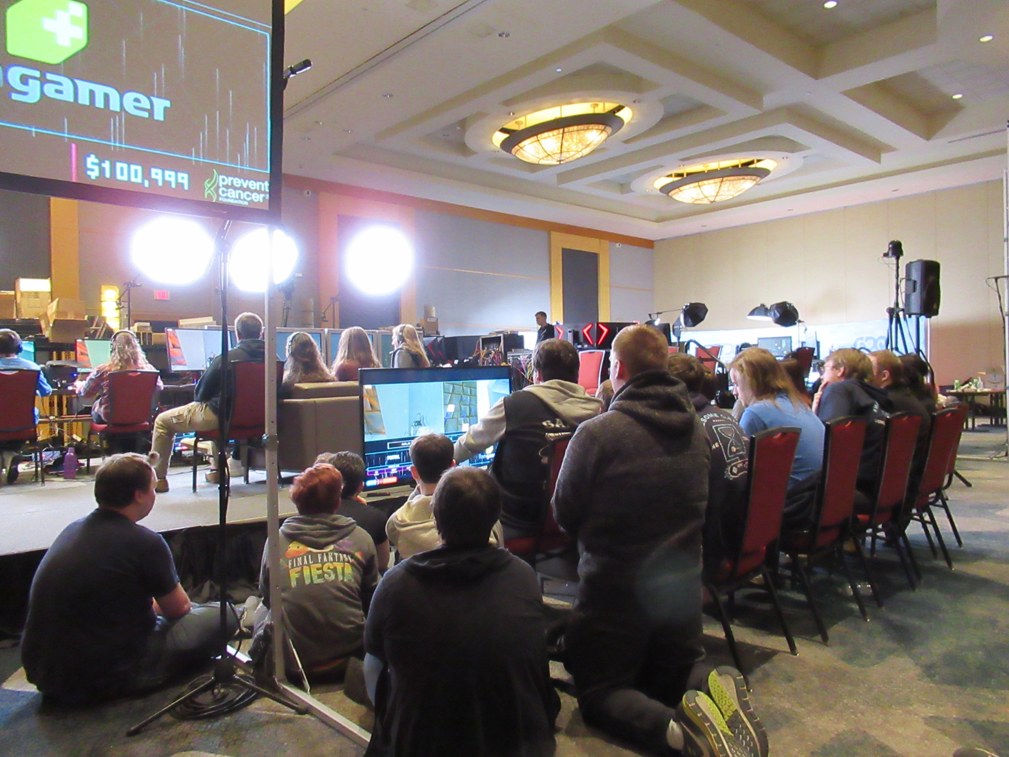 A gathering of people behind the stage of GDQ around the backup couch. The backup couch is positioned in front of a TV.