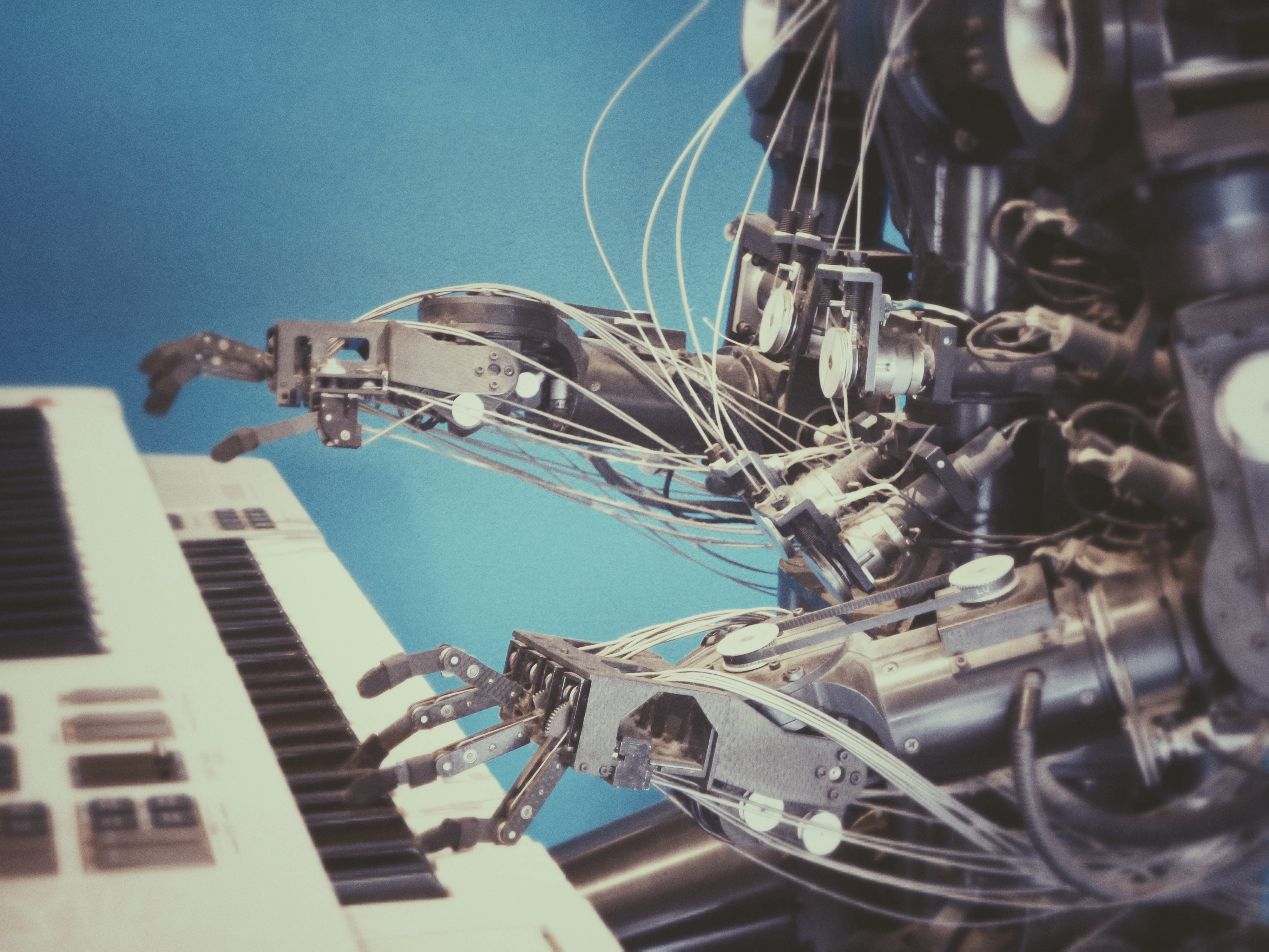A robot seated at a piano with its hands hovering over the keys