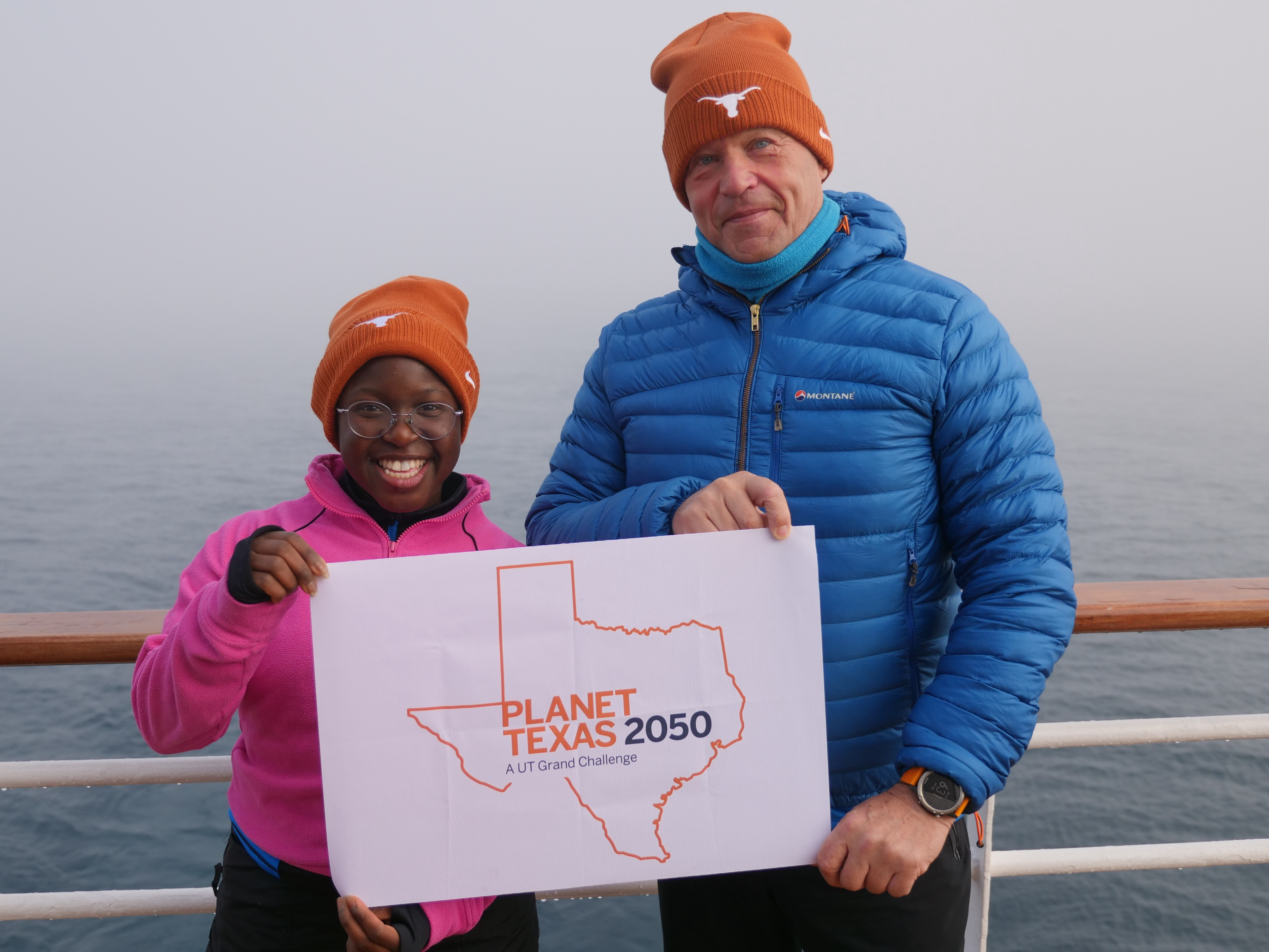 UT student Seyi Odufuye and explorer Robert Swan wear Longhorn hats and stand on the ship holding a Planet Texas 2050 flag.