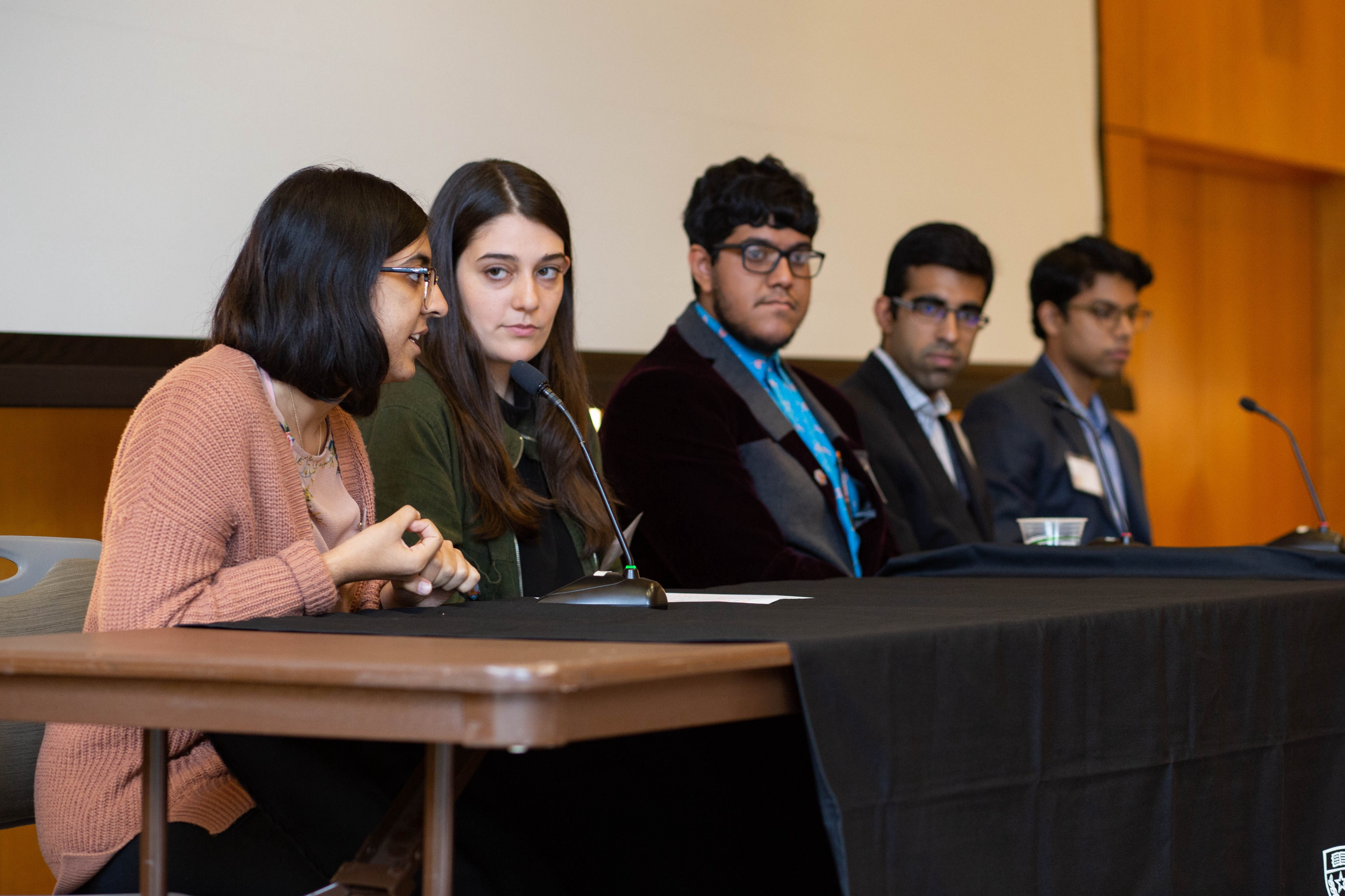 Five students sit in front of microphones at a table in a conference room.