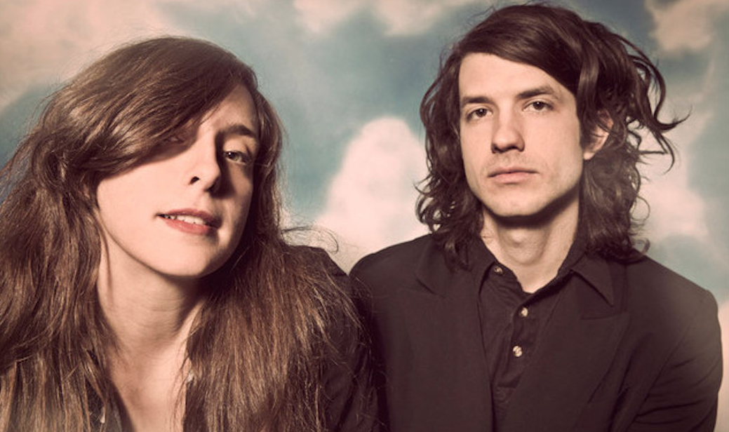 "alt=""Beach House band poses with clouds in background"""