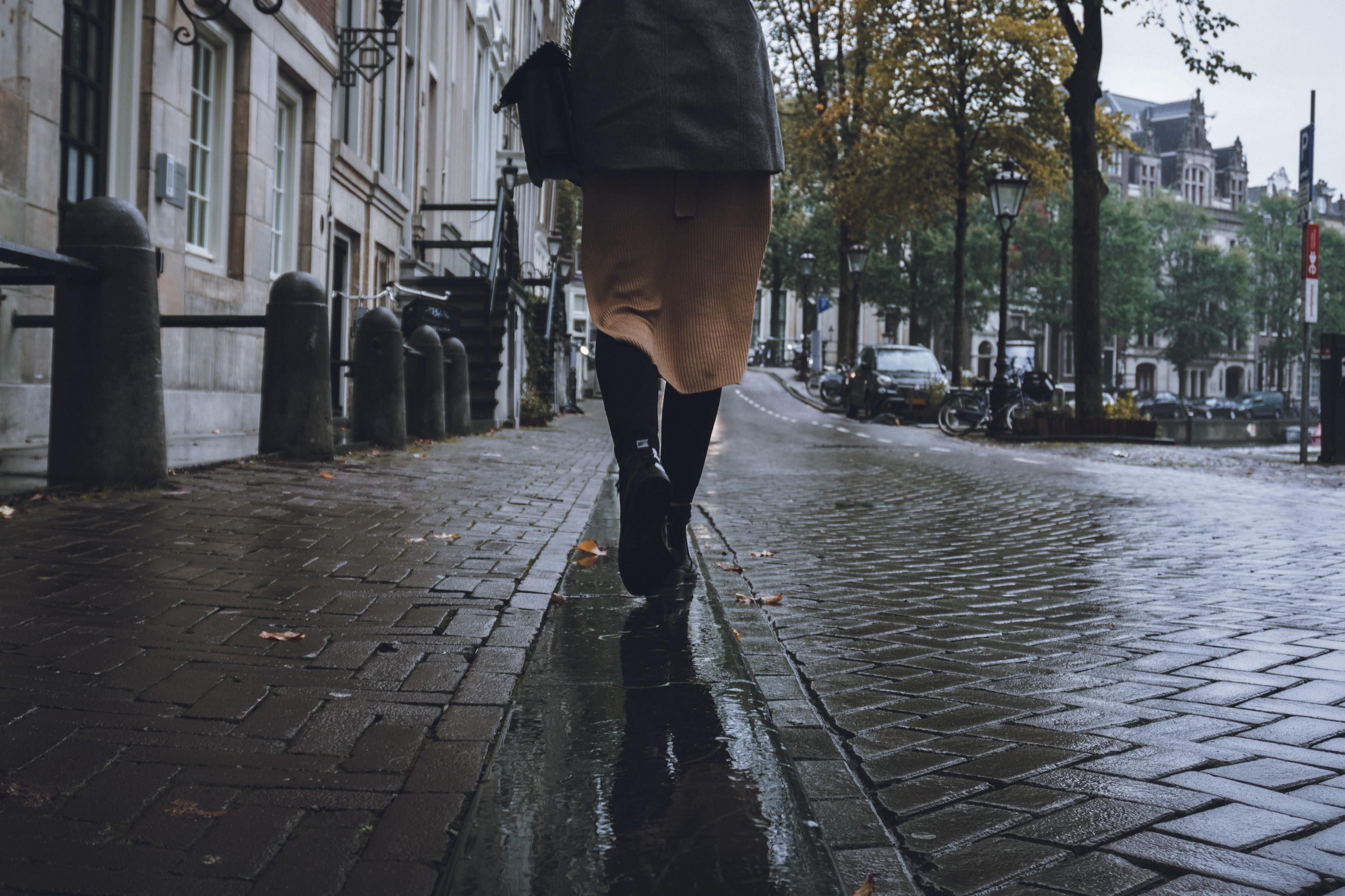 photo of a woman walking away from the camera down a cobblestone city street.