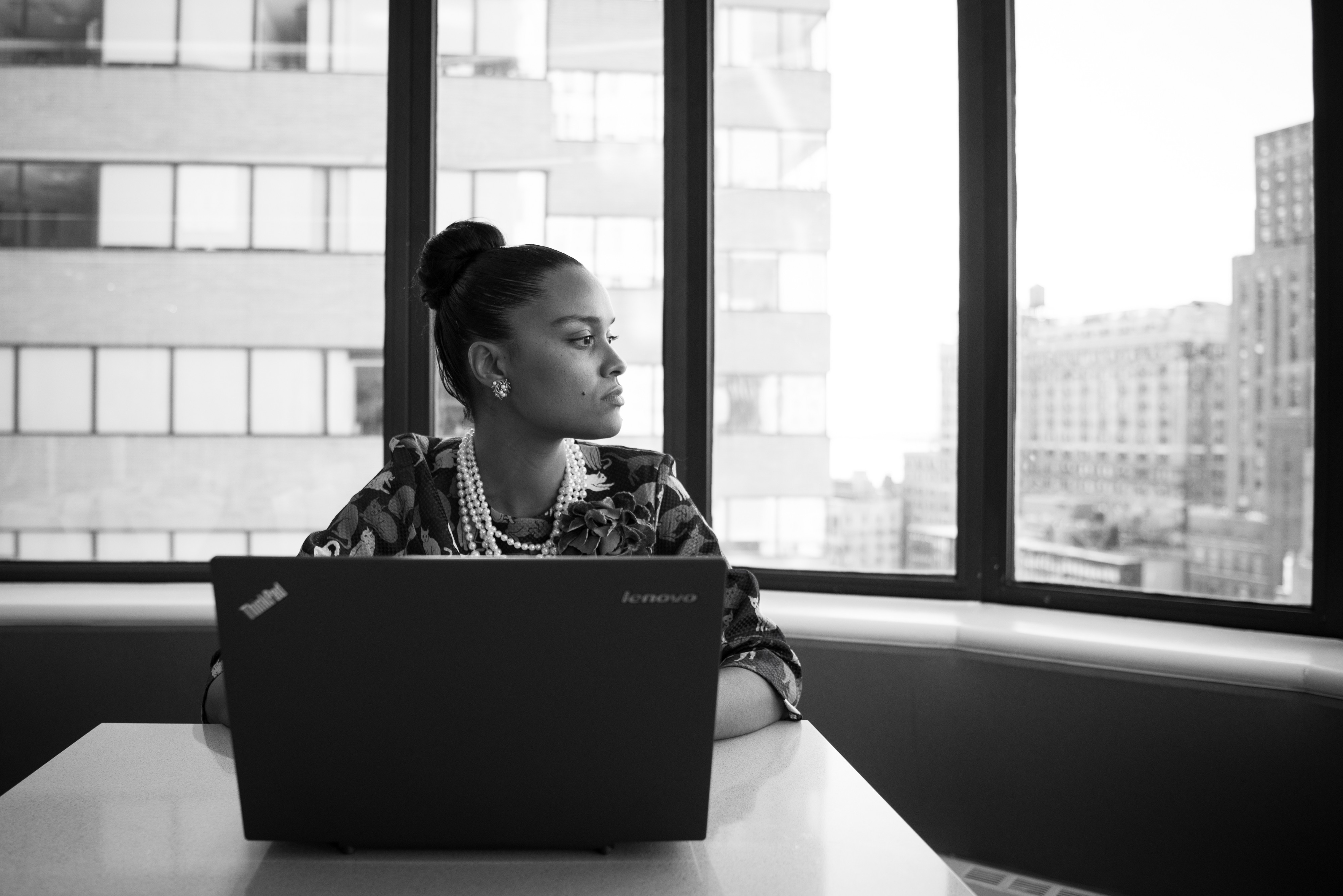 Woman of color sitting in a windowed corner office working on a laptop
