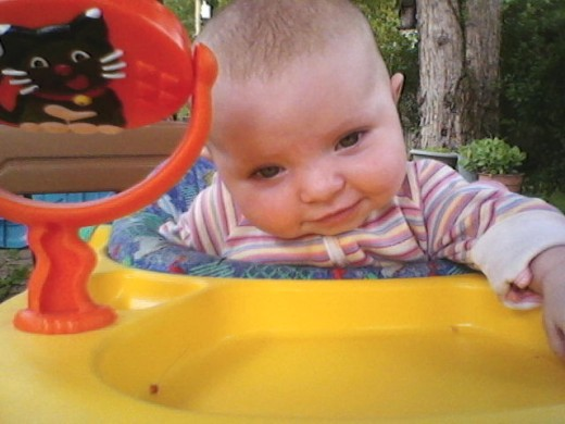 Baby sitting outside, playing in a bouncy seat