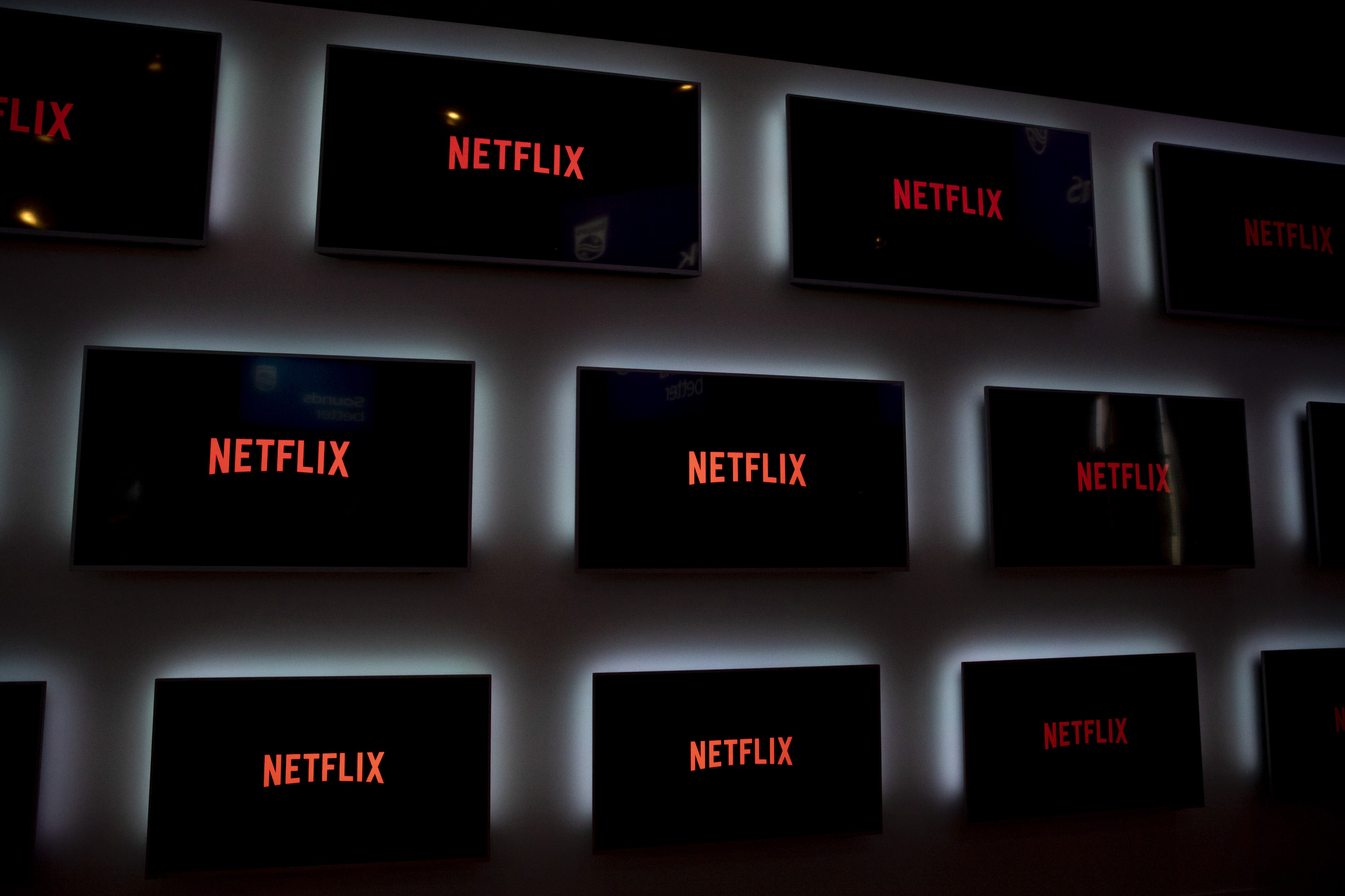 Display monitors with Netflix logo are pictured against a black background.