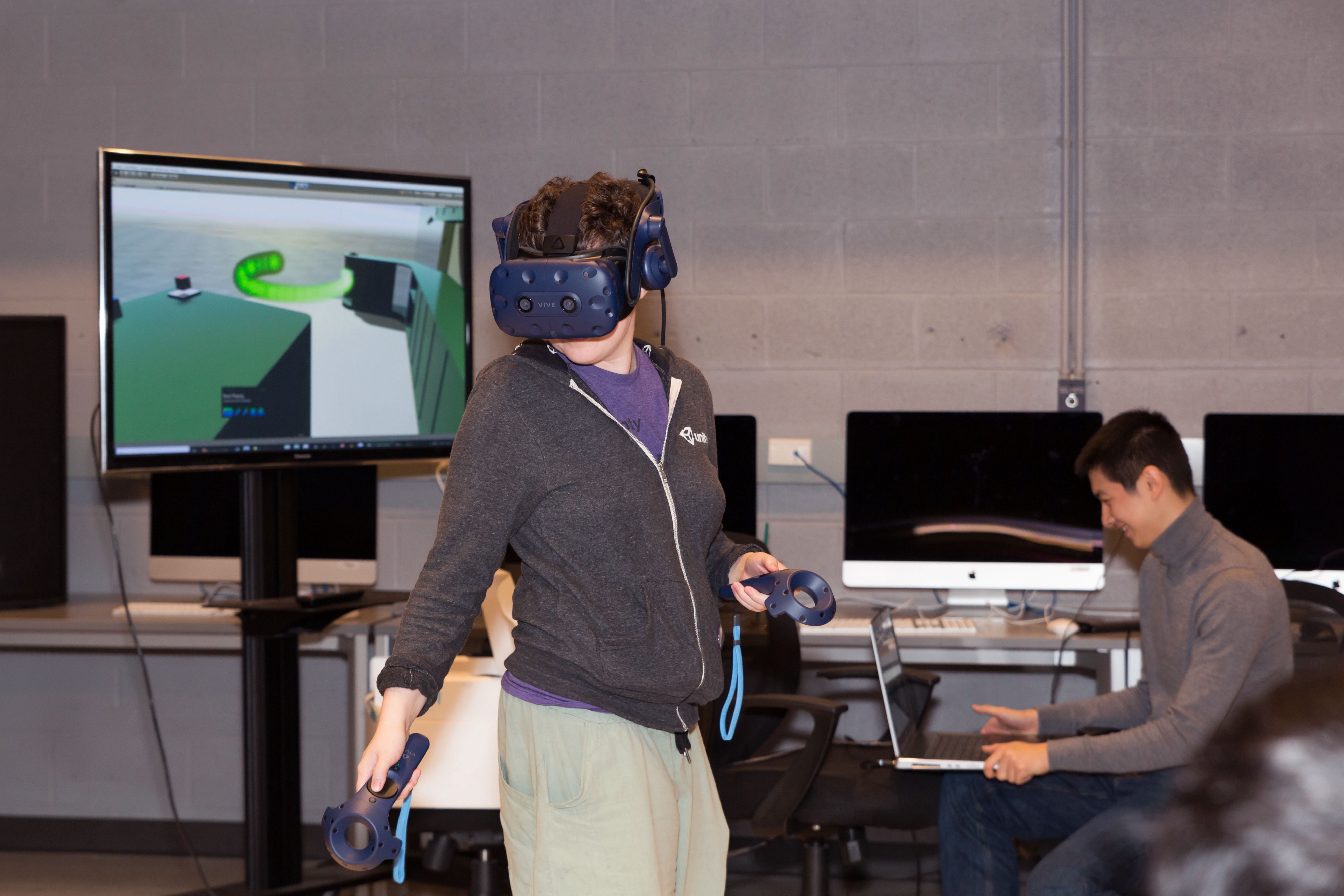 A UT Arts and Entertainment Technologies assistant professor wears a VR headset to try a Planet Texas 2050-inspired VR game.