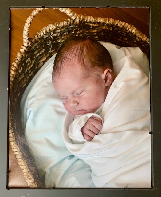 Photo of newborn baby sleeping in basket with ivory sheets.