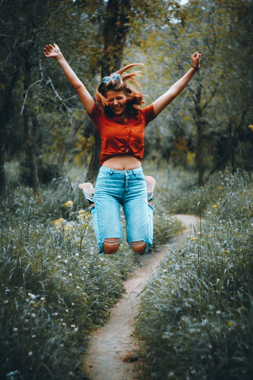 A woman jumps high and happily in the forest.