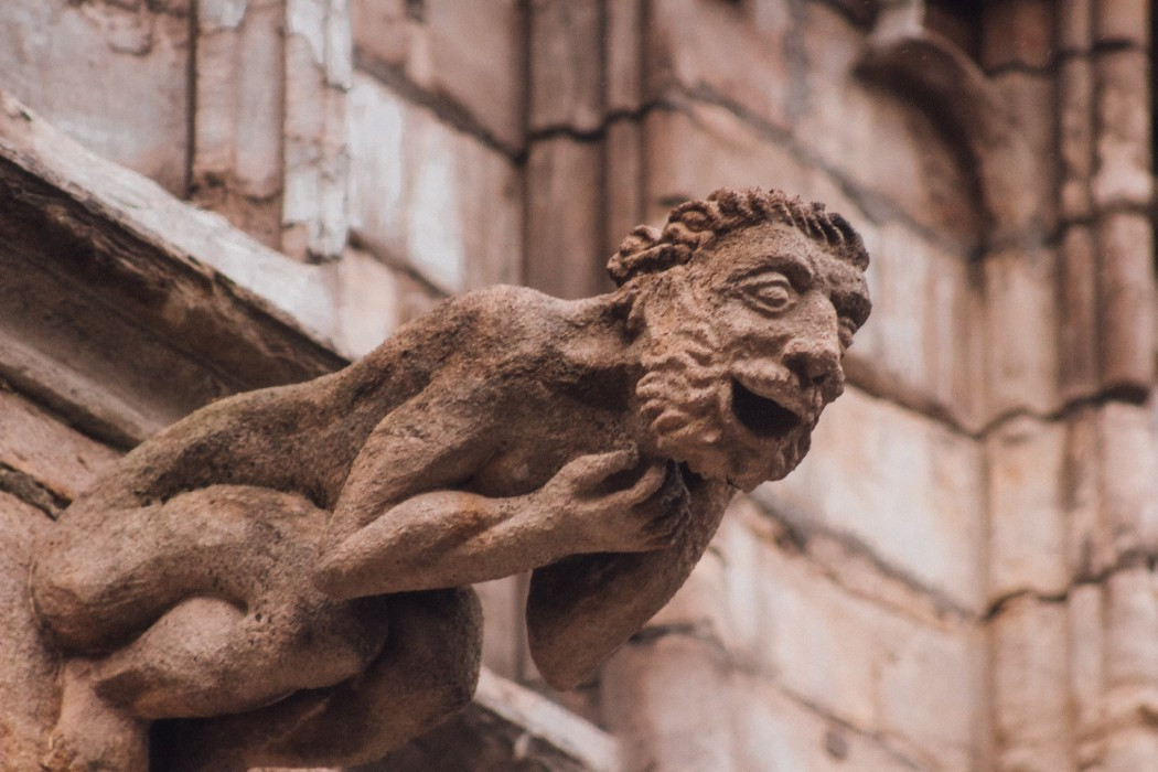 What appears to be a laughing gargoyle of a naked man stroking his beard, face and body jutting out from an old stone building.