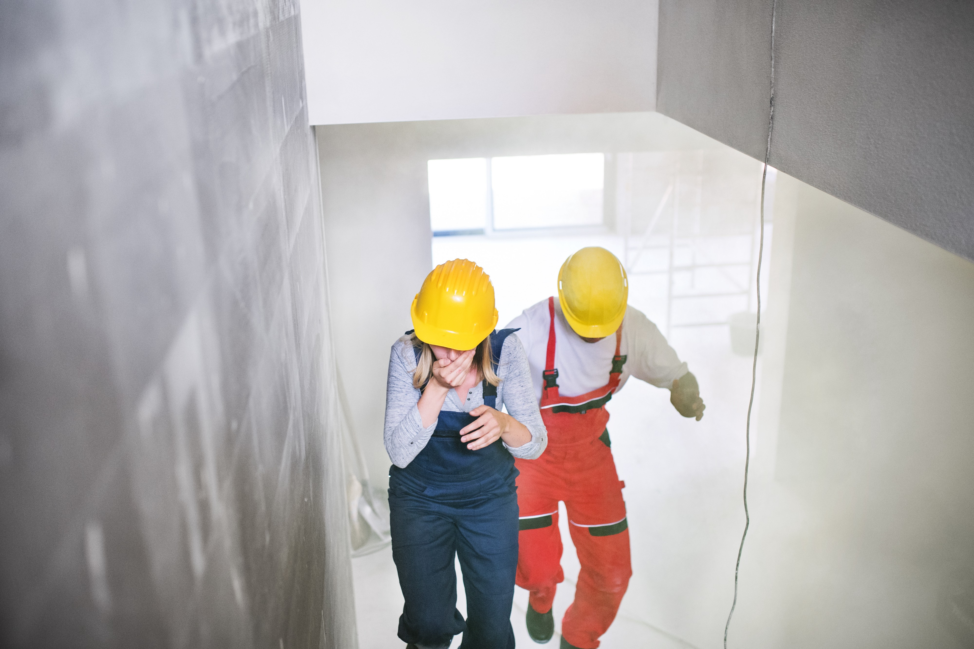 A woman and a man in construction clothes are running upstairs through dust while coughing at a worksite.