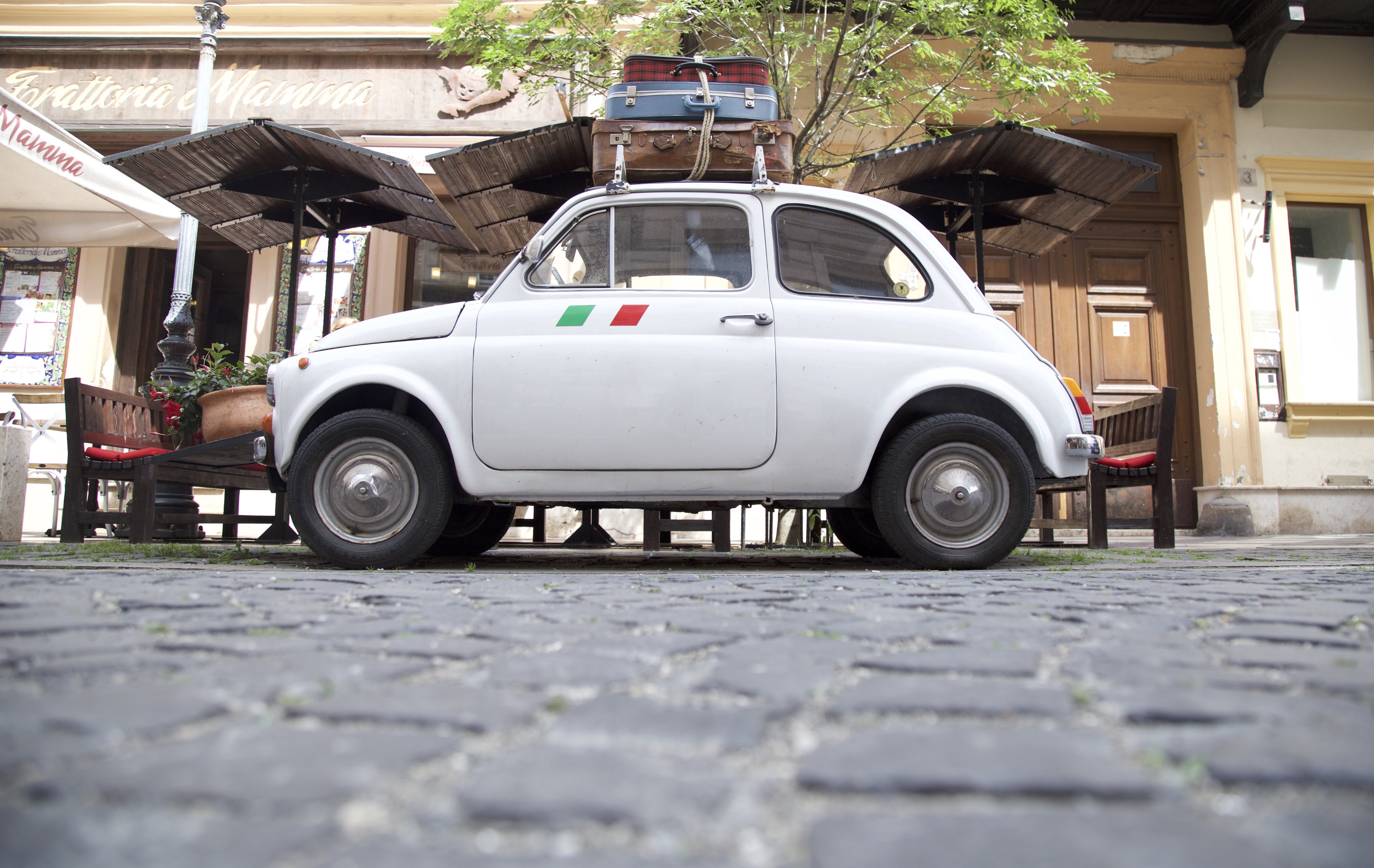 old tiny Fiat with suitcase attached on top on a cobblestone street and an Italian flag sticker