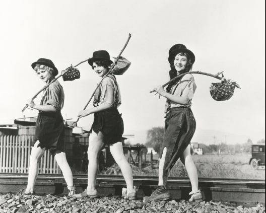 Three women walking along railroad tracks, carrying bindle sticks