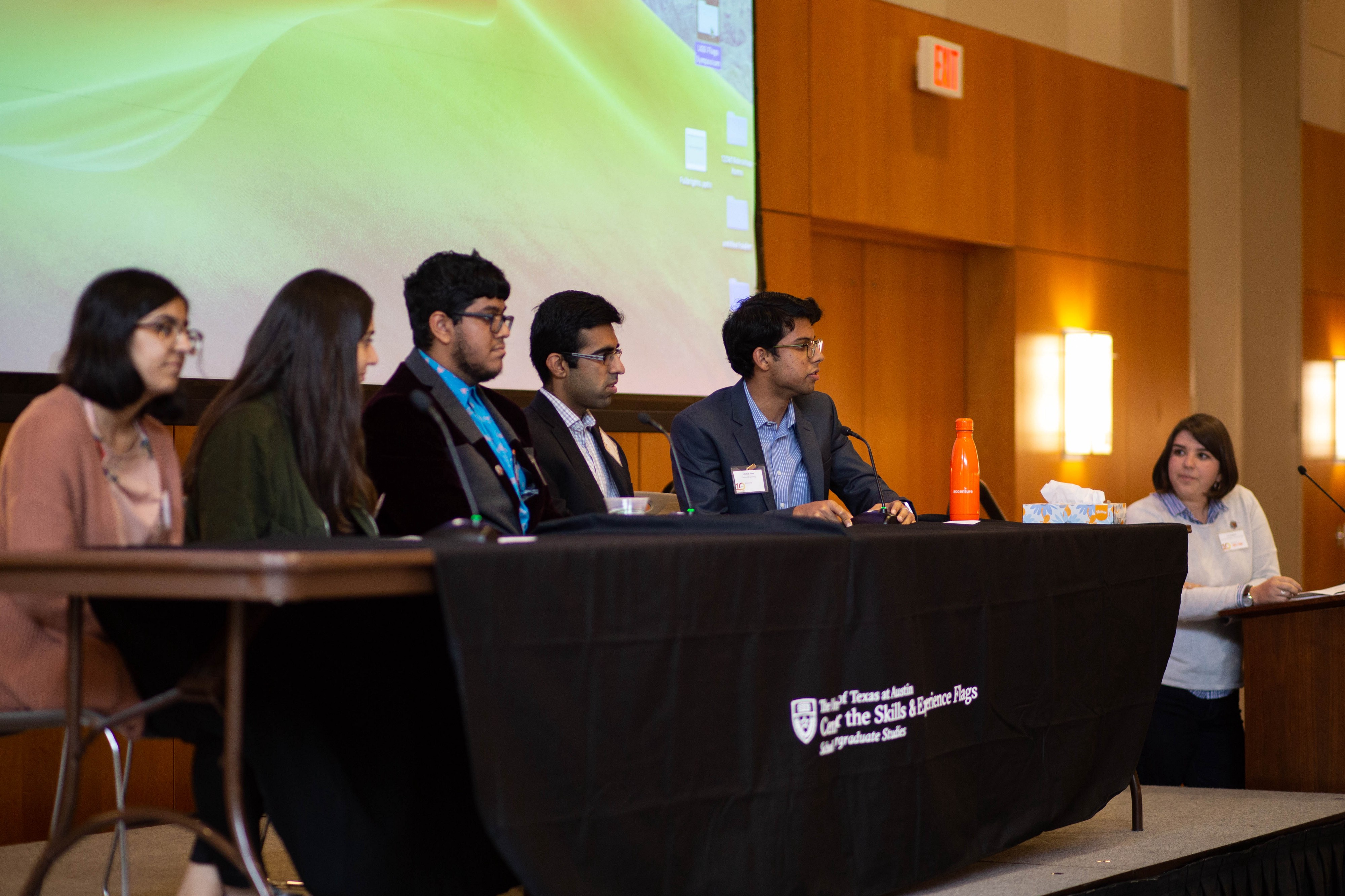 Five students sit in front of microphones at a table in a conference room. The panel moderator stand to the right of them.