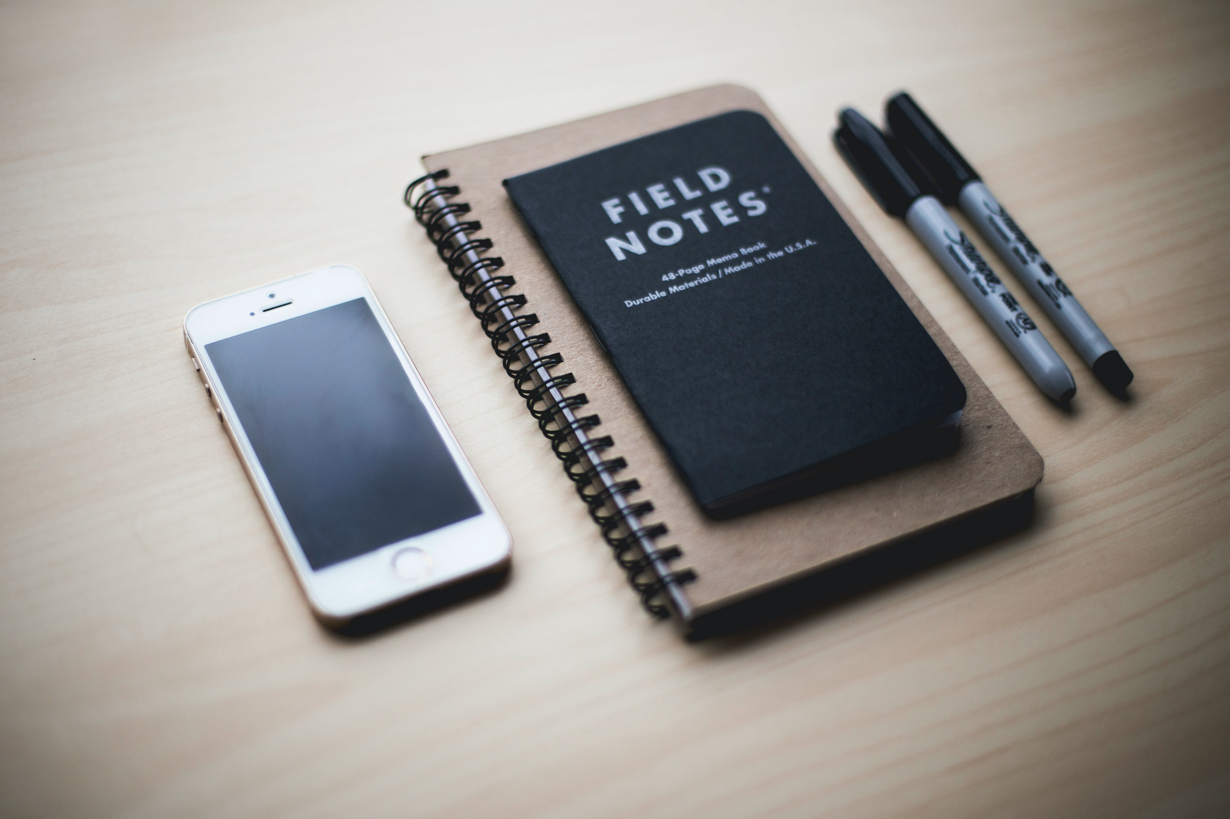 Image of table with cell phone, notebook, pens, and a booklet entitled Field Notes