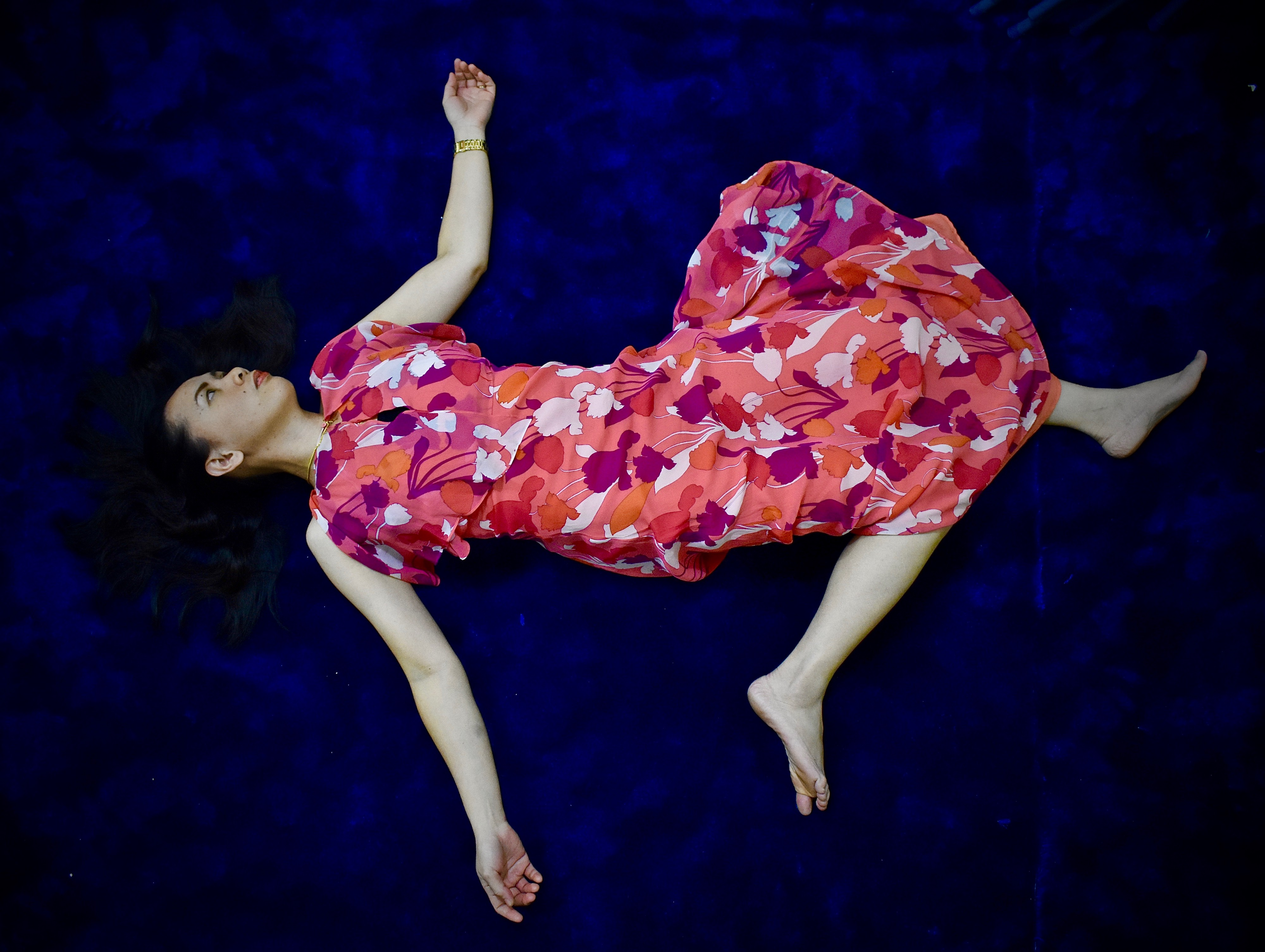 A bird's aye view of a woman in pink dress lying on the carpet