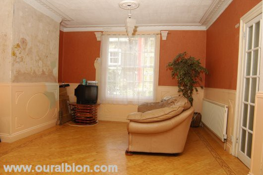 A lounge, spacious for London, with a nice looking floor, paint swatches on the panelling and a few pieces of furniture.