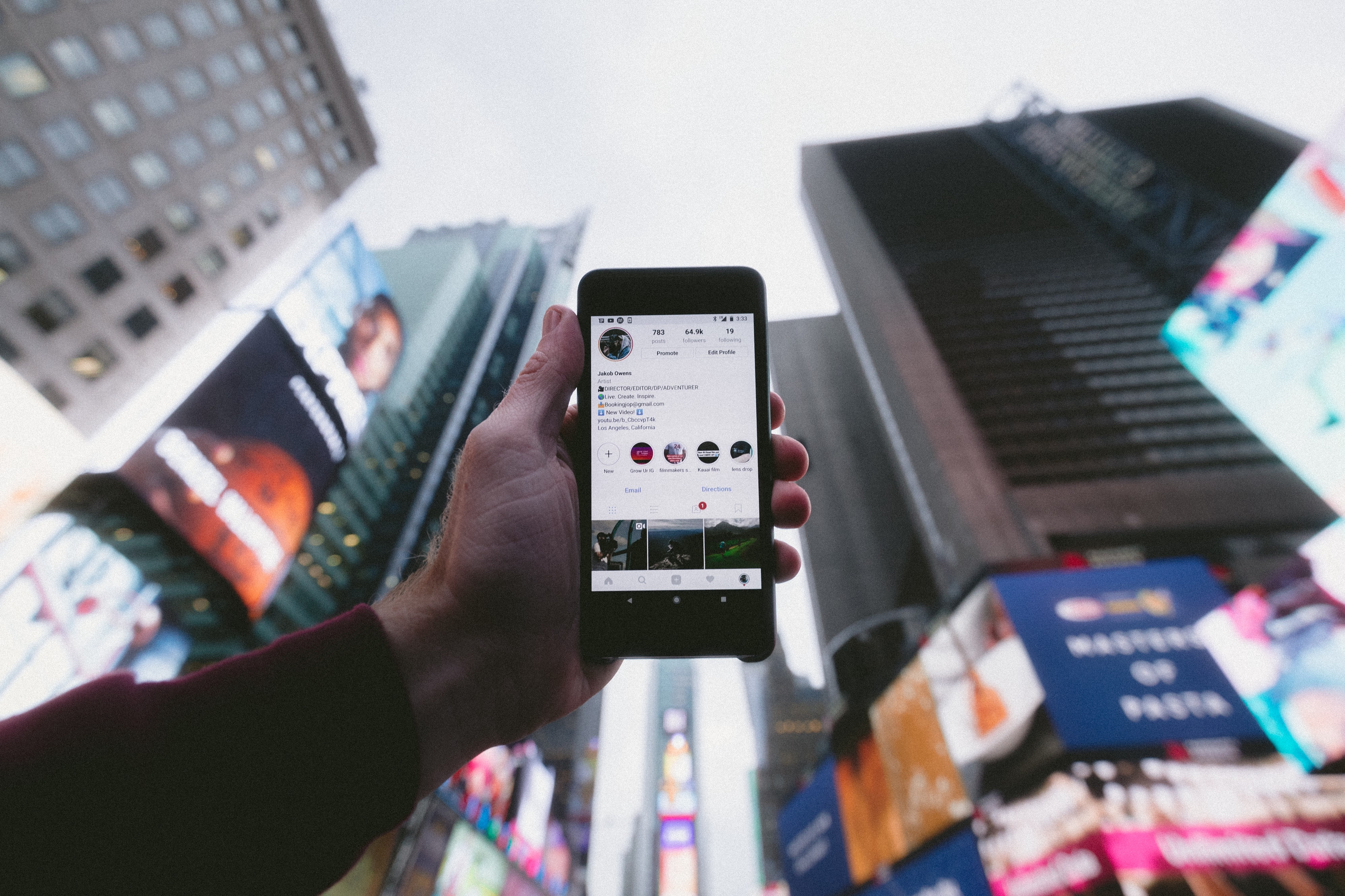 Hand holding phone featuring Instagram profile in front of Times Square in New York City.