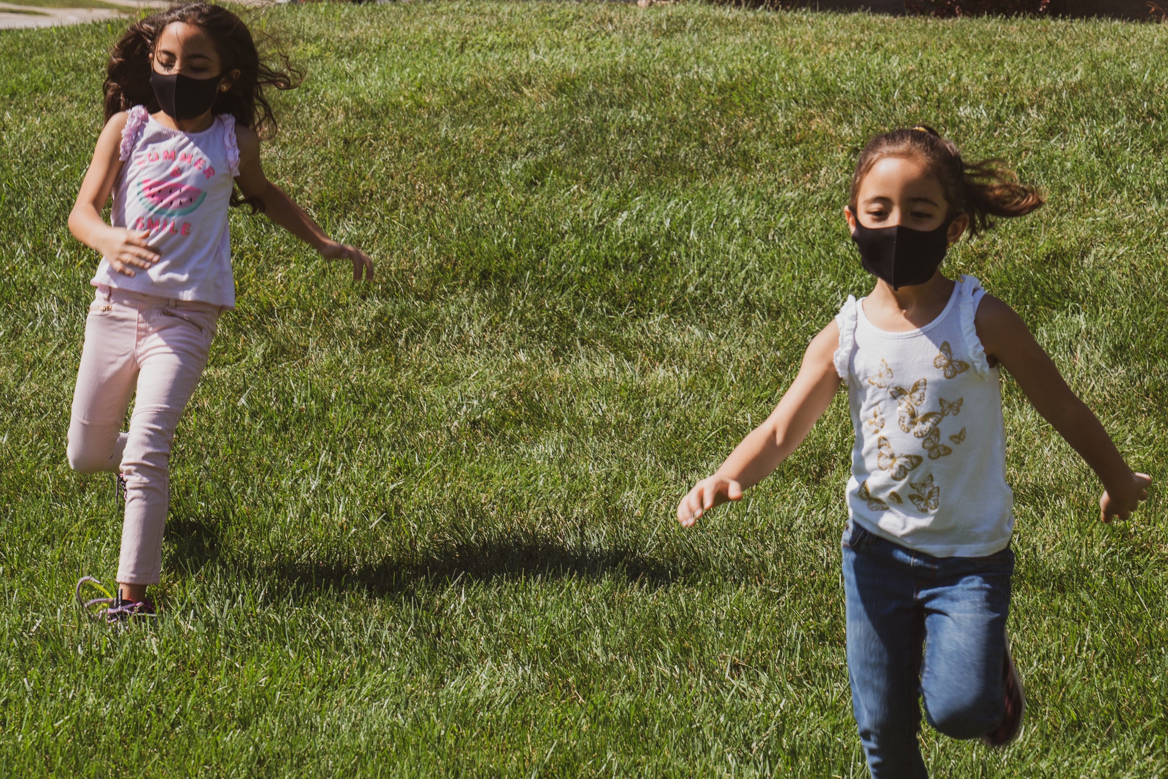 Two young children play outside while wearing COVID-19 face masks.