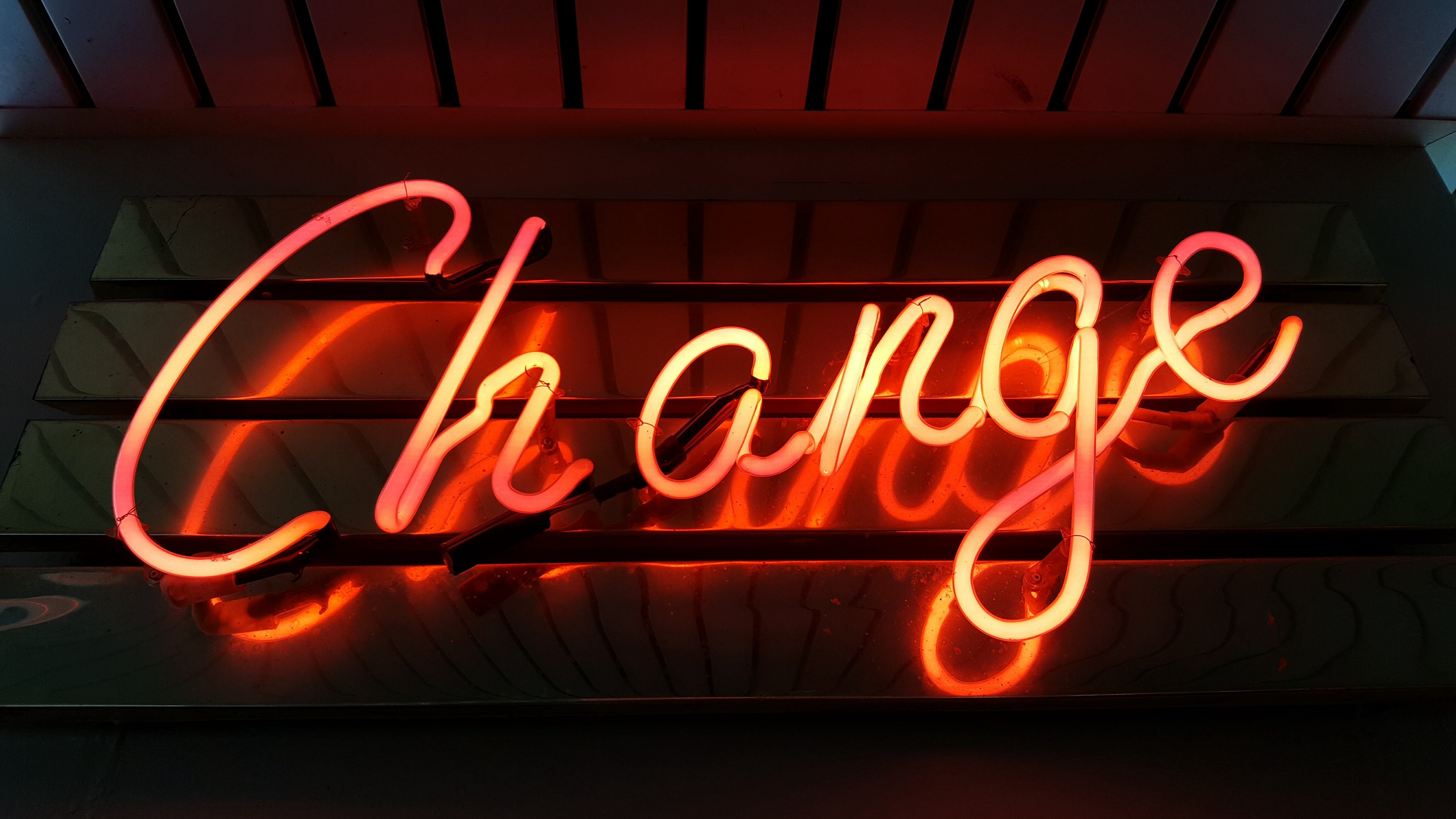 """Orange colored neon sign with the word """"change""""."""