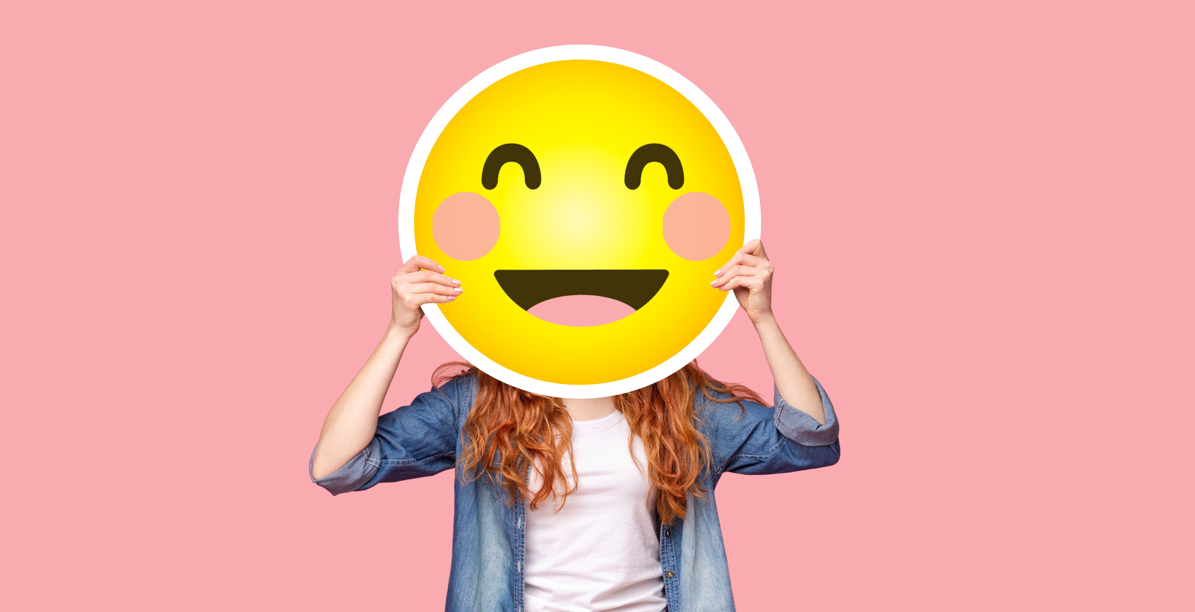 Woman hiding behind a happy face sign