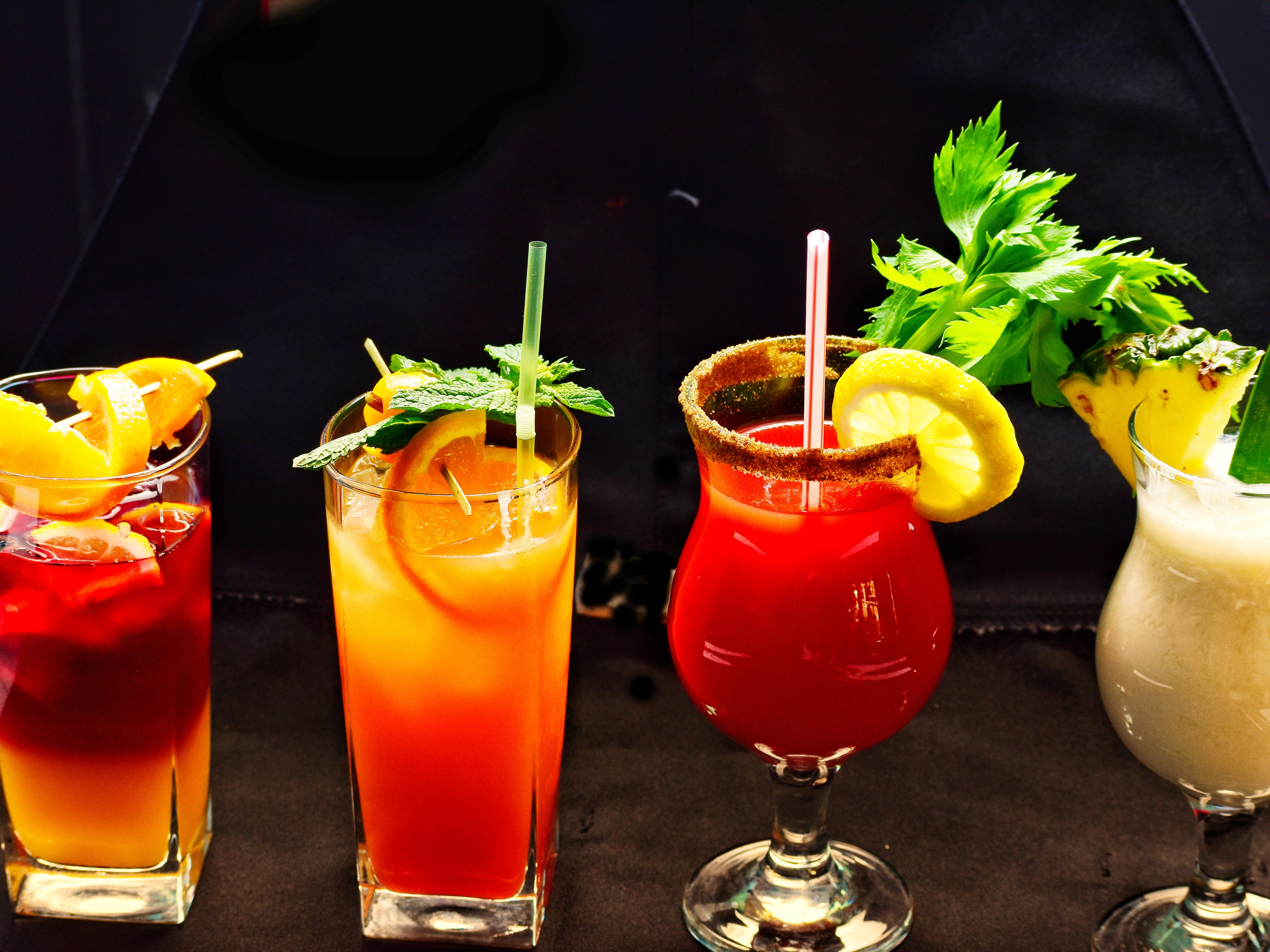 Four different glasses of brightly colored mixed cocktails, with a variety of garnishes