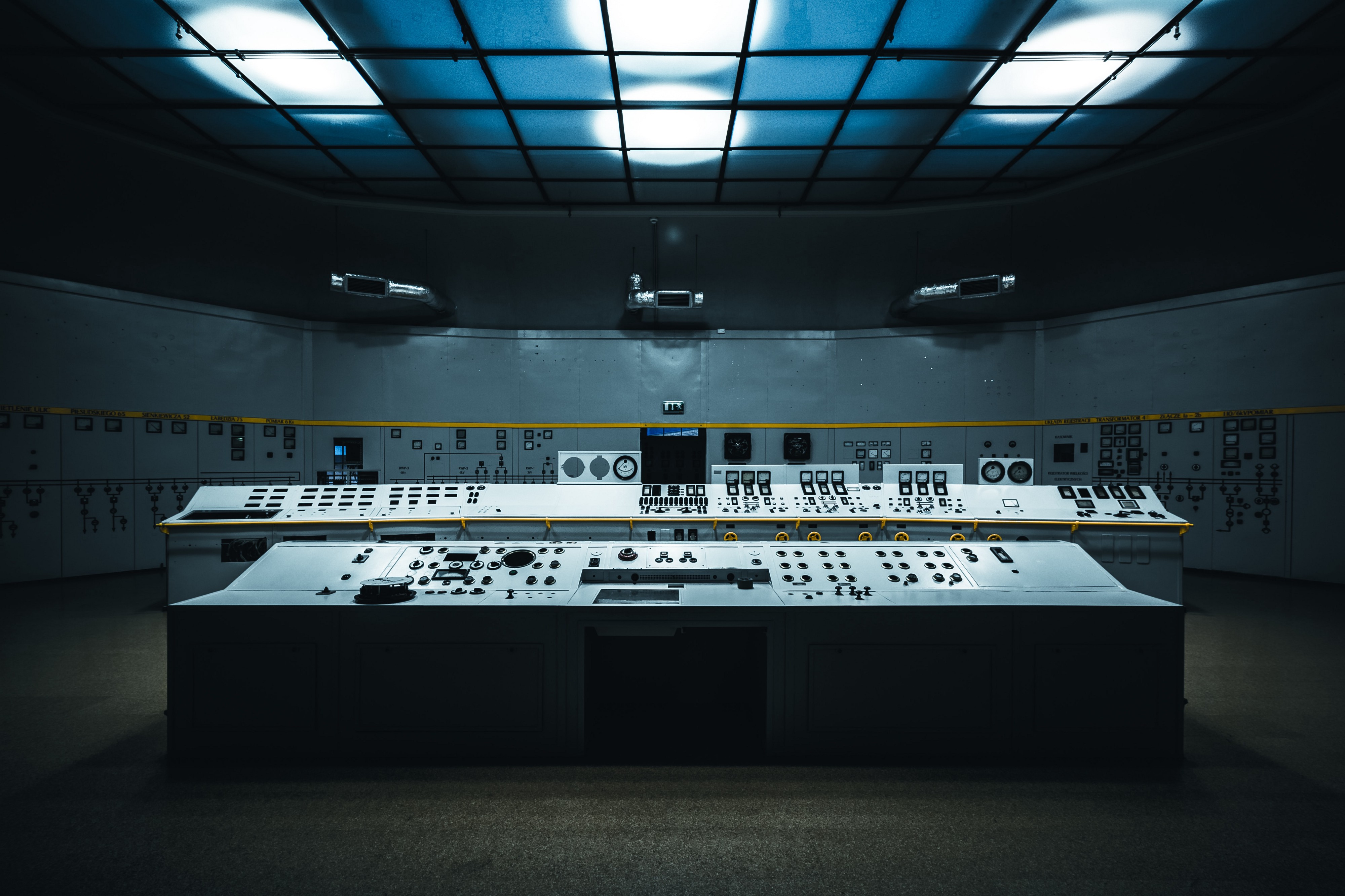 A dark and empty control room with digital controls and computer screens