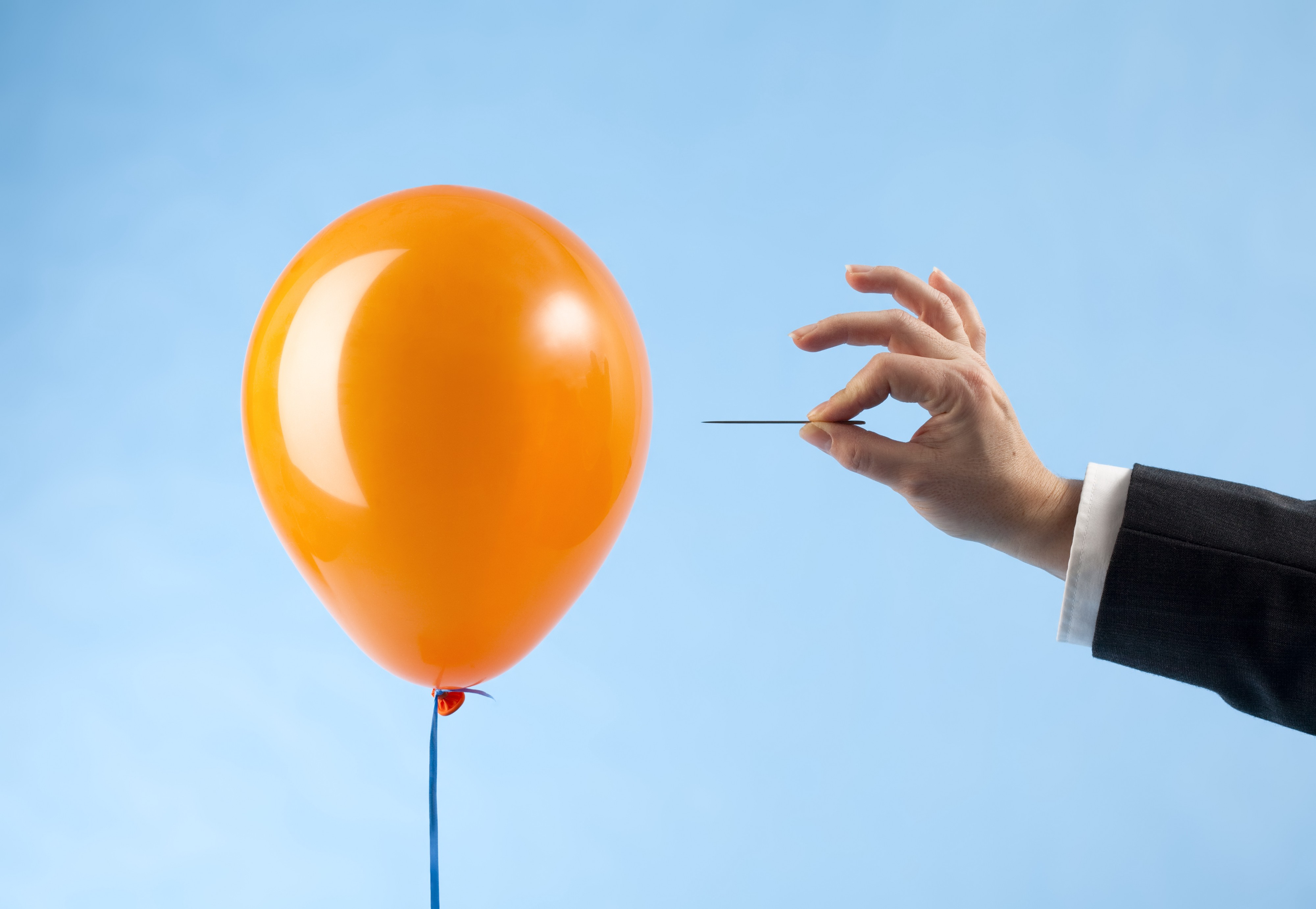 A balloon about to be popped with a needle.