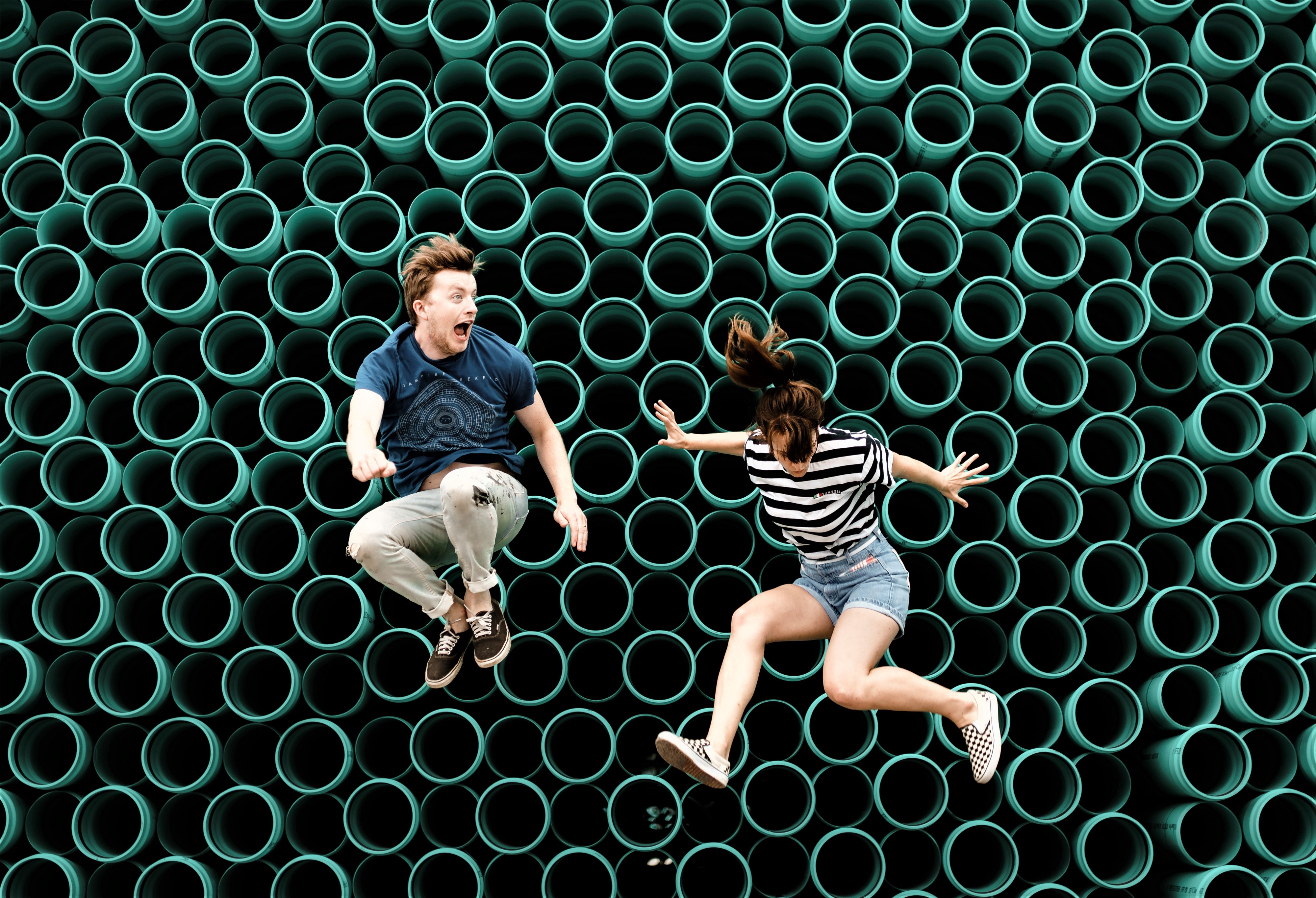 boy and girl jumping in air wall of green round tubes behind them