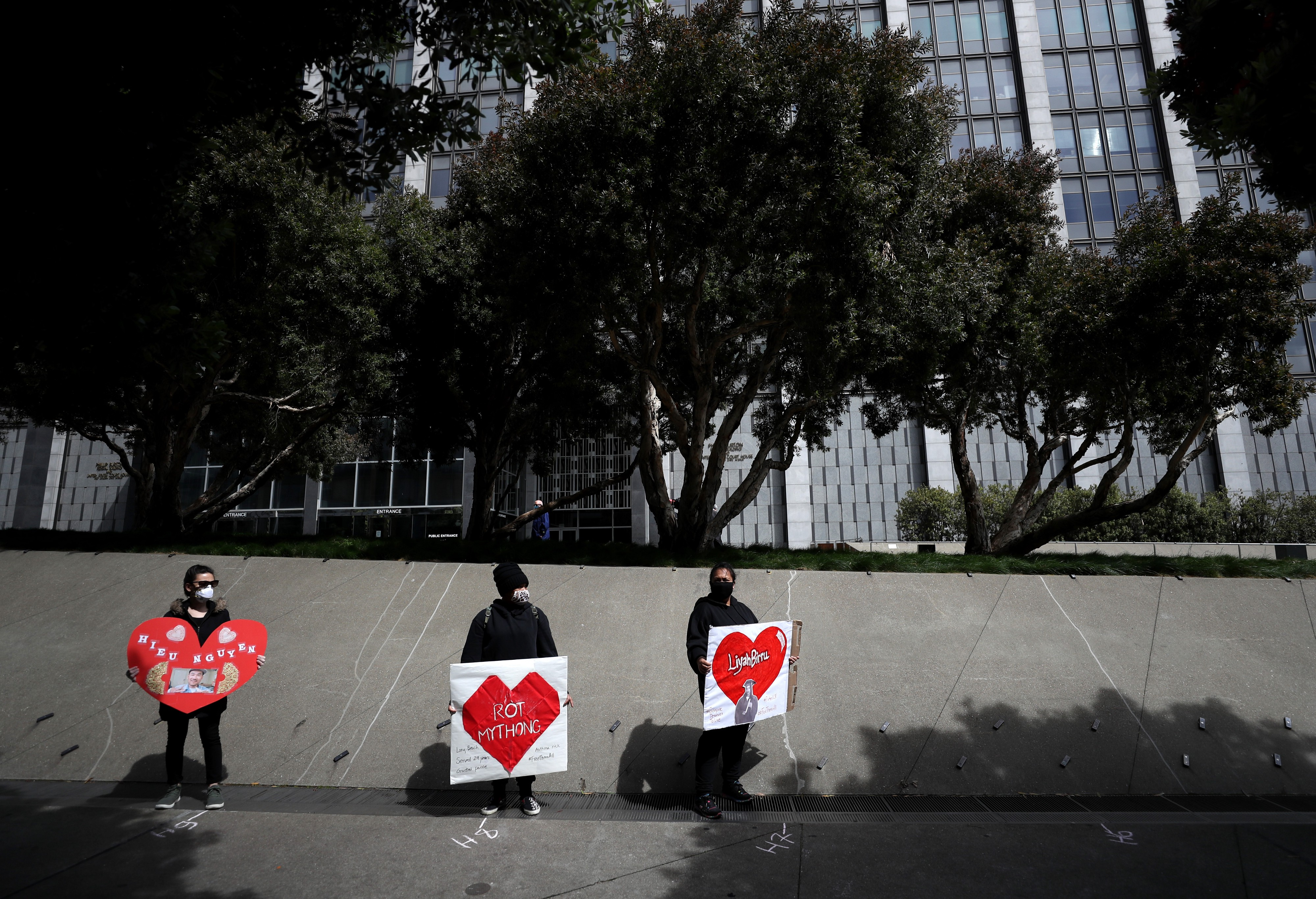 Activists hold signs and tombstone shapes in front of the Phillip Burton Federal Building to honor Covid-19 victims.