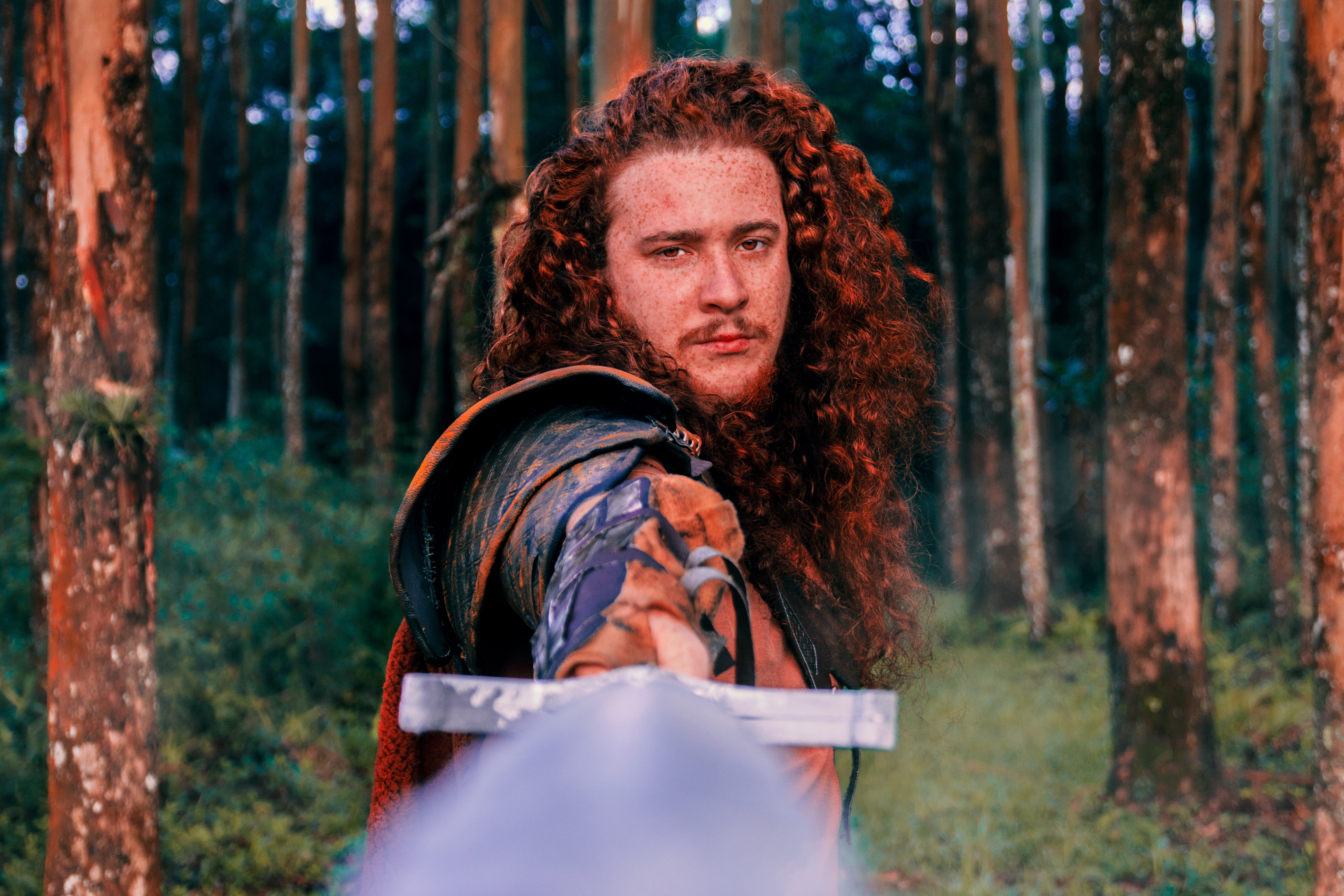 A male knight with long curly red hair holds his sword forwards toward the camera