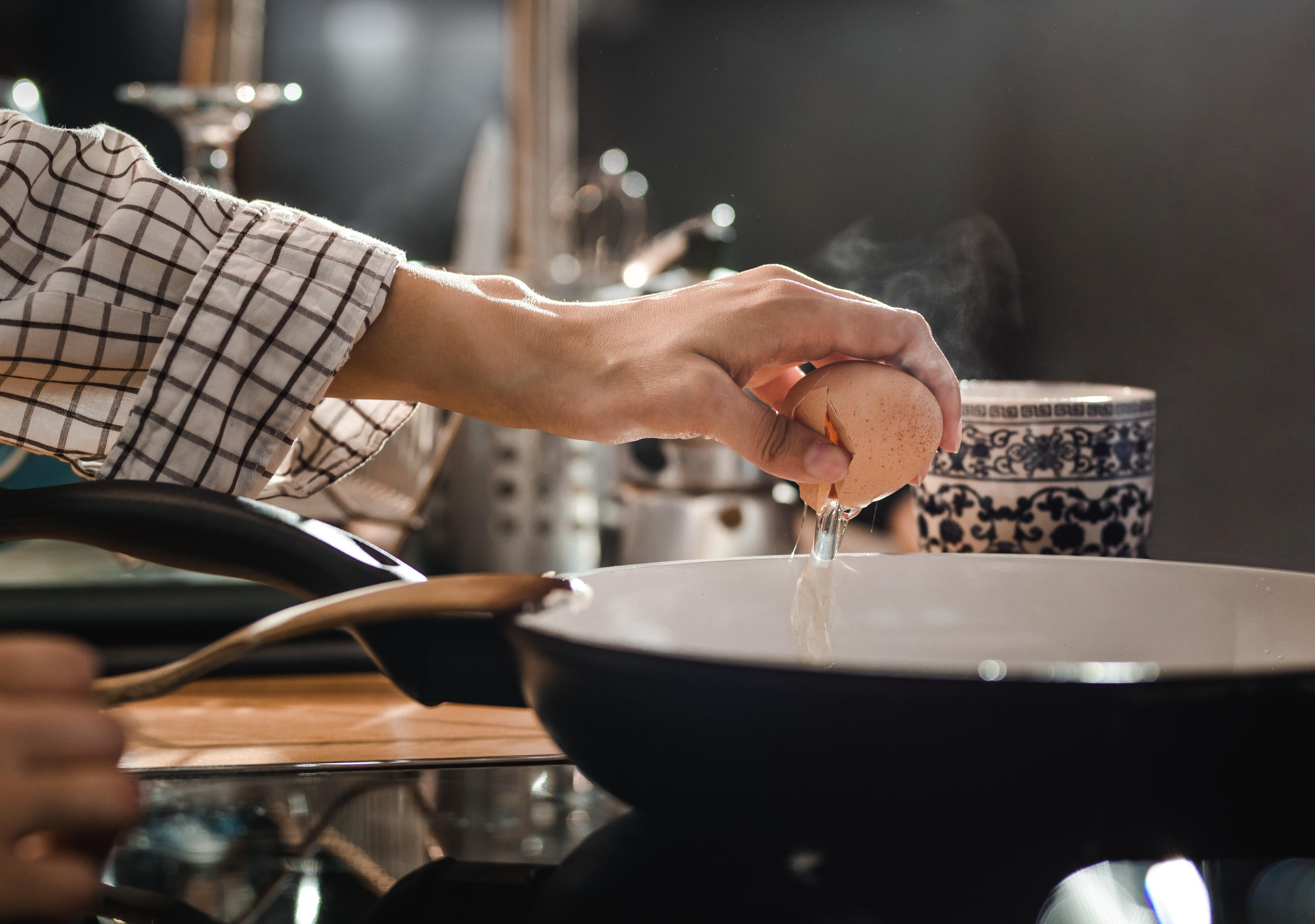 Close up of unrecognizable woman cracking an egg for breakfast while putting it in a frying pan.
