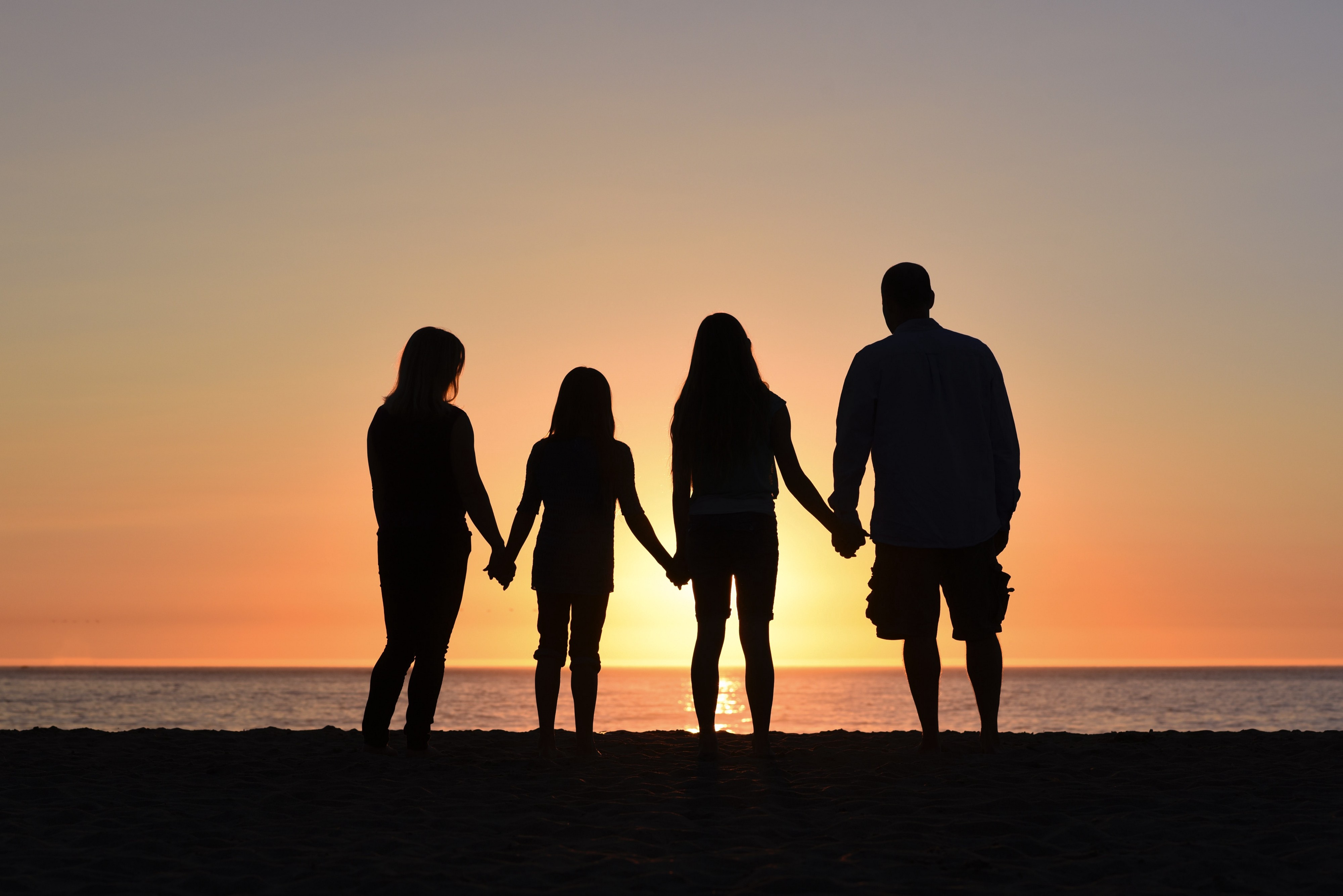 silouhette of family of four holding hands, standing on beach in front of the ocean at sunset