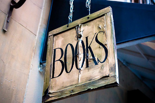 Wooden sign that reads BOOKS in all caps hanging outside a building.