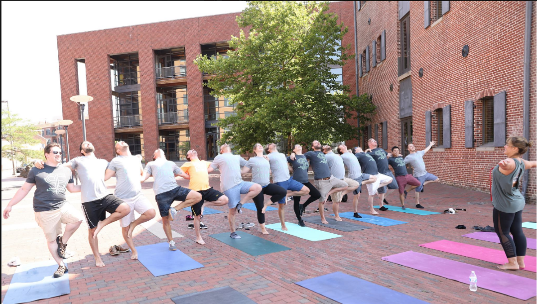 Think|Stack team doing yoga on Baltimore's waterfront