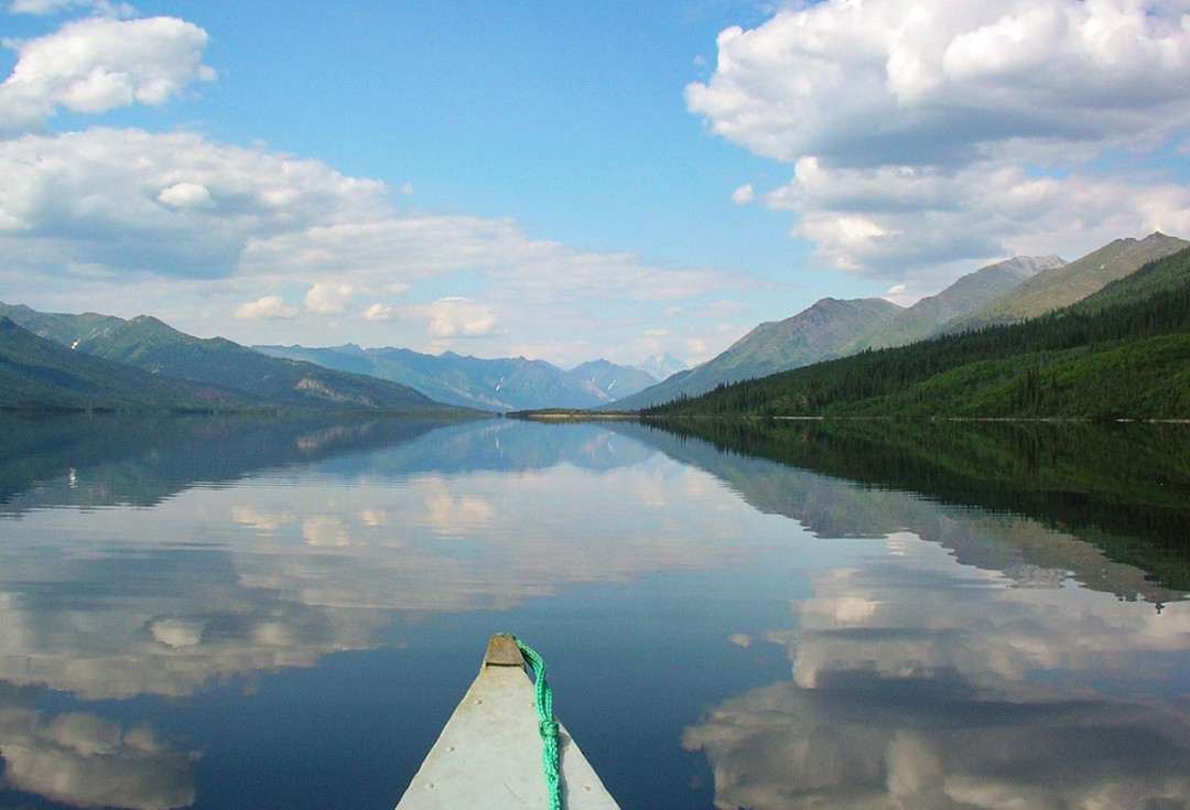 View of a lake from a boat or canoe. There are mountains in the background and a partly cloudy sky above.