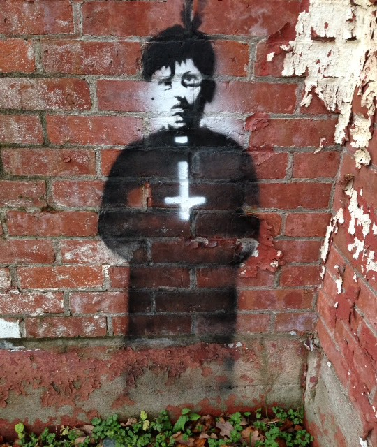 The image of an Indigenous altar-boy holding an upside-down cross is graffitied onto the crumbling bricks of St. Michael's Indian Residential School in Alert Bay, B.C.
