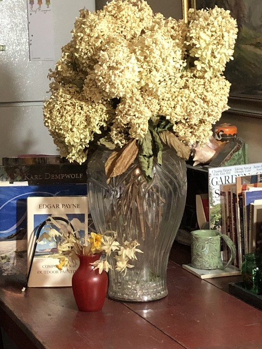 Old red kitchen table with a glass vase of dried limelight hydrangeas, books about art, and a coffee mug.
