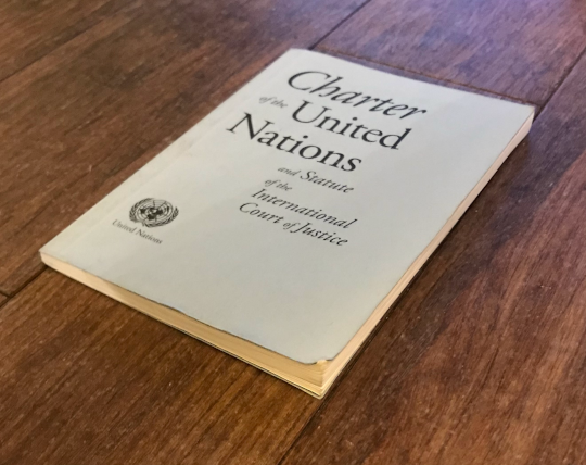 The Charter of the United Nations is viewed at a shallow angle. The book's shape in the image is an irregular quadrilateral.