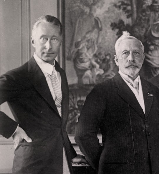 Wilhelm and his father wearing dark suits. Wilhelm is very tan. His father's hair and beard are white.
