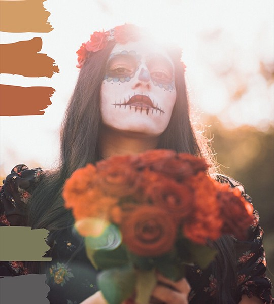 A woman dressed in day-of-the-dead makeup holding red roses. Painted bars on the left show a fall Halloween mood board.