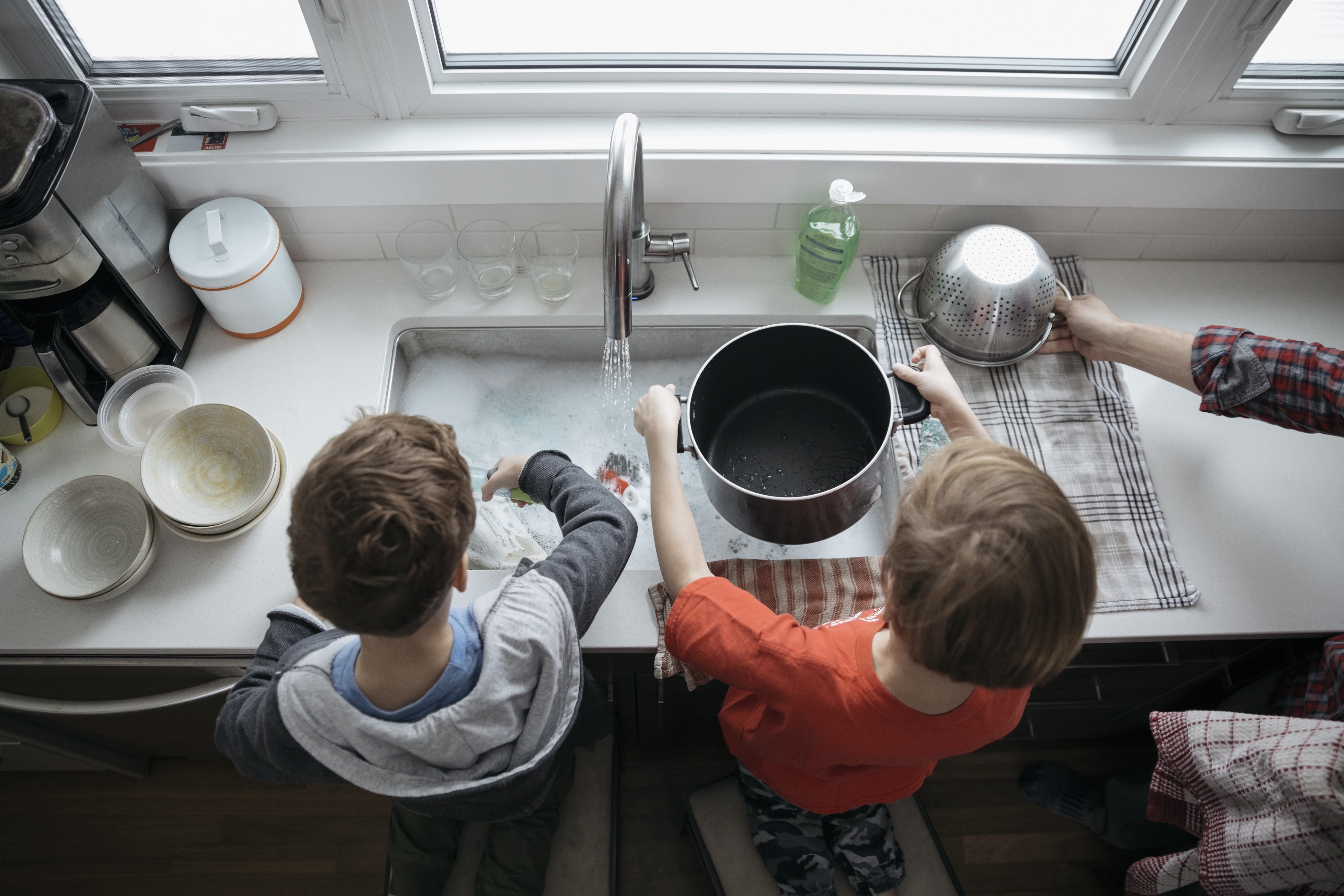 Overhead view of brothers doing dishes at the kitchen sink.