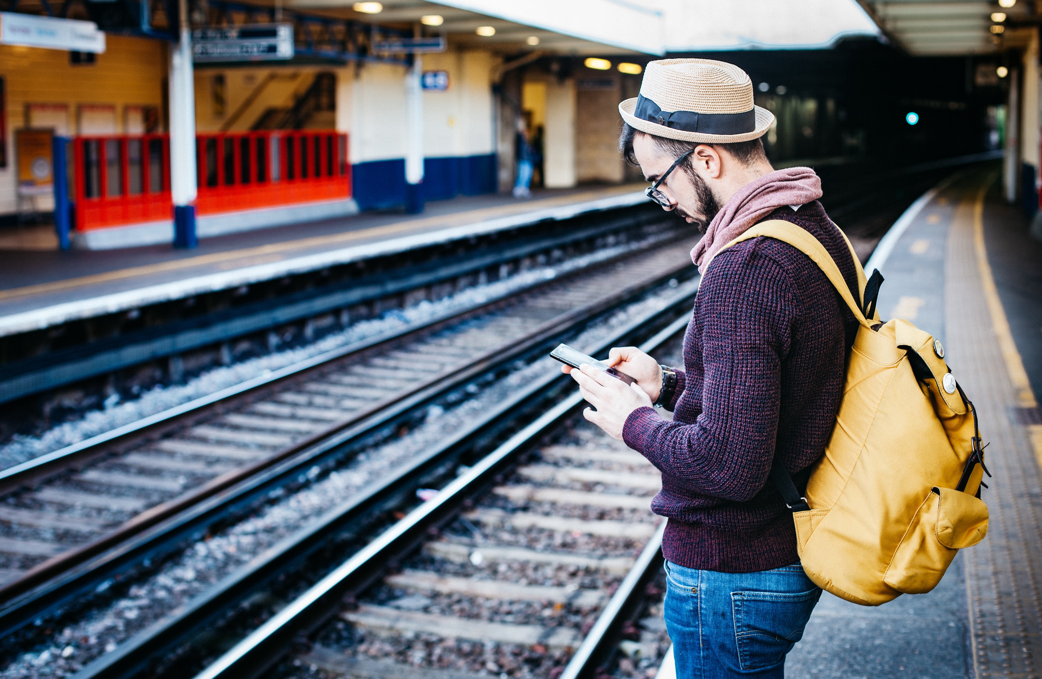The picture shows a person standing in a station, looking at his smartphone.